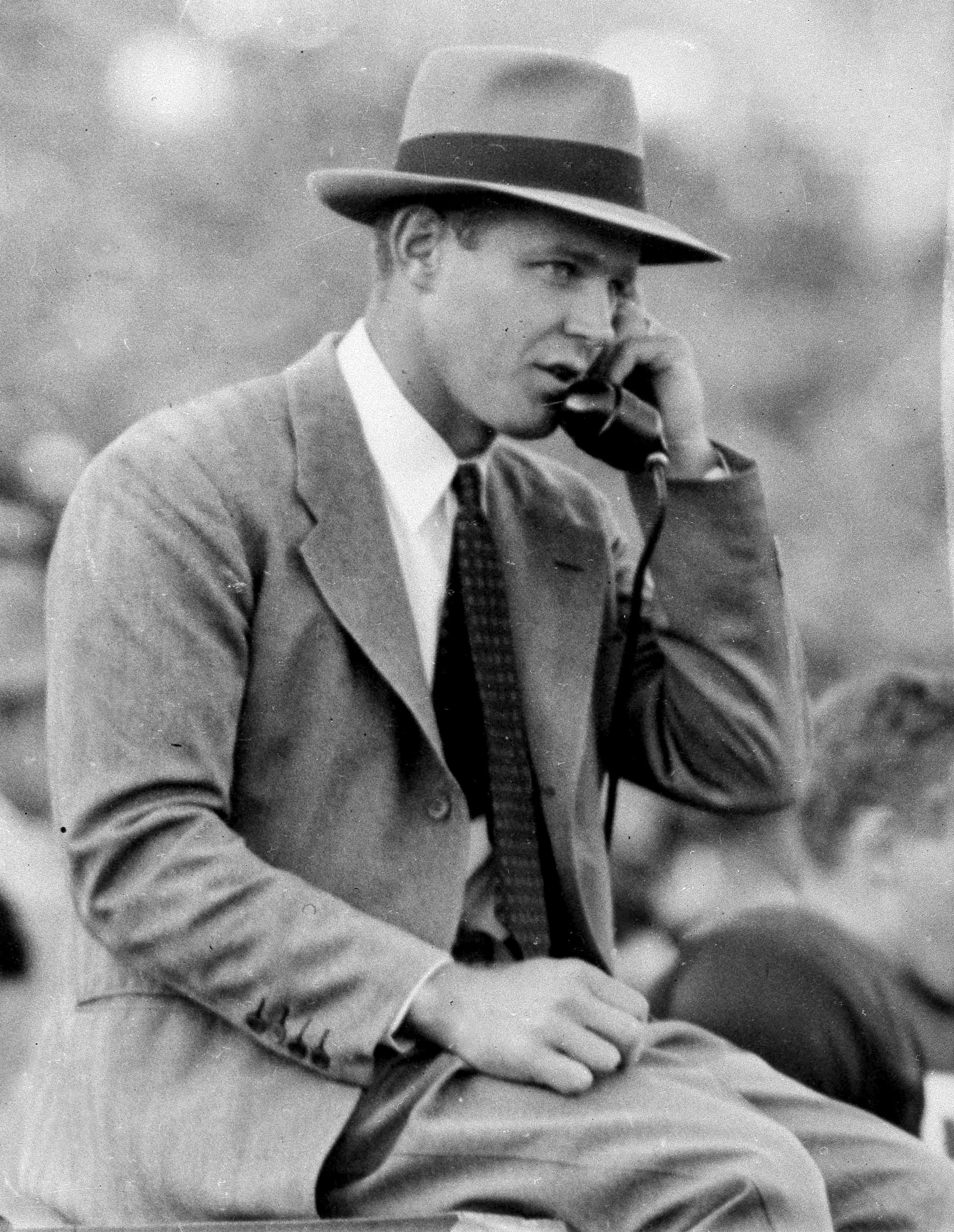 FILE - In this Nov. 1949 file photo, Oklahoma coach Bud Wilkinson talks on the sideline on a phone during a college football game in Norman, Okla. By the 1950s, college football's balance of power had drifted away from the elite eastern schools and into t