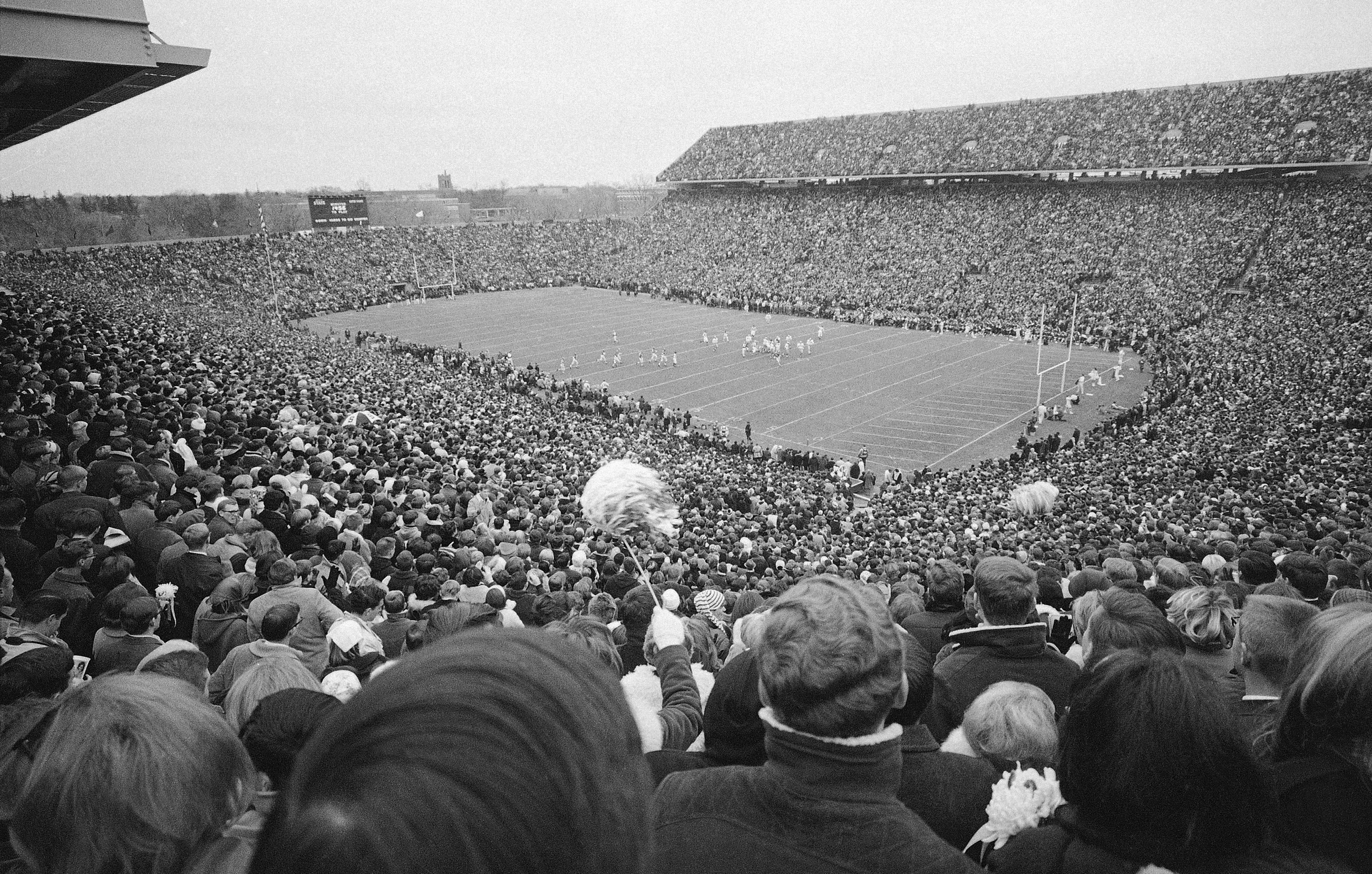 FILE - In this Nov. 19, 1966, file photo, an overflow crowd, estimated at more than 80,000, watch the Michigan State against Notre Dame college football game in East Lansing, Mich. It was the final regular-season game for Michigan State and second-to-last