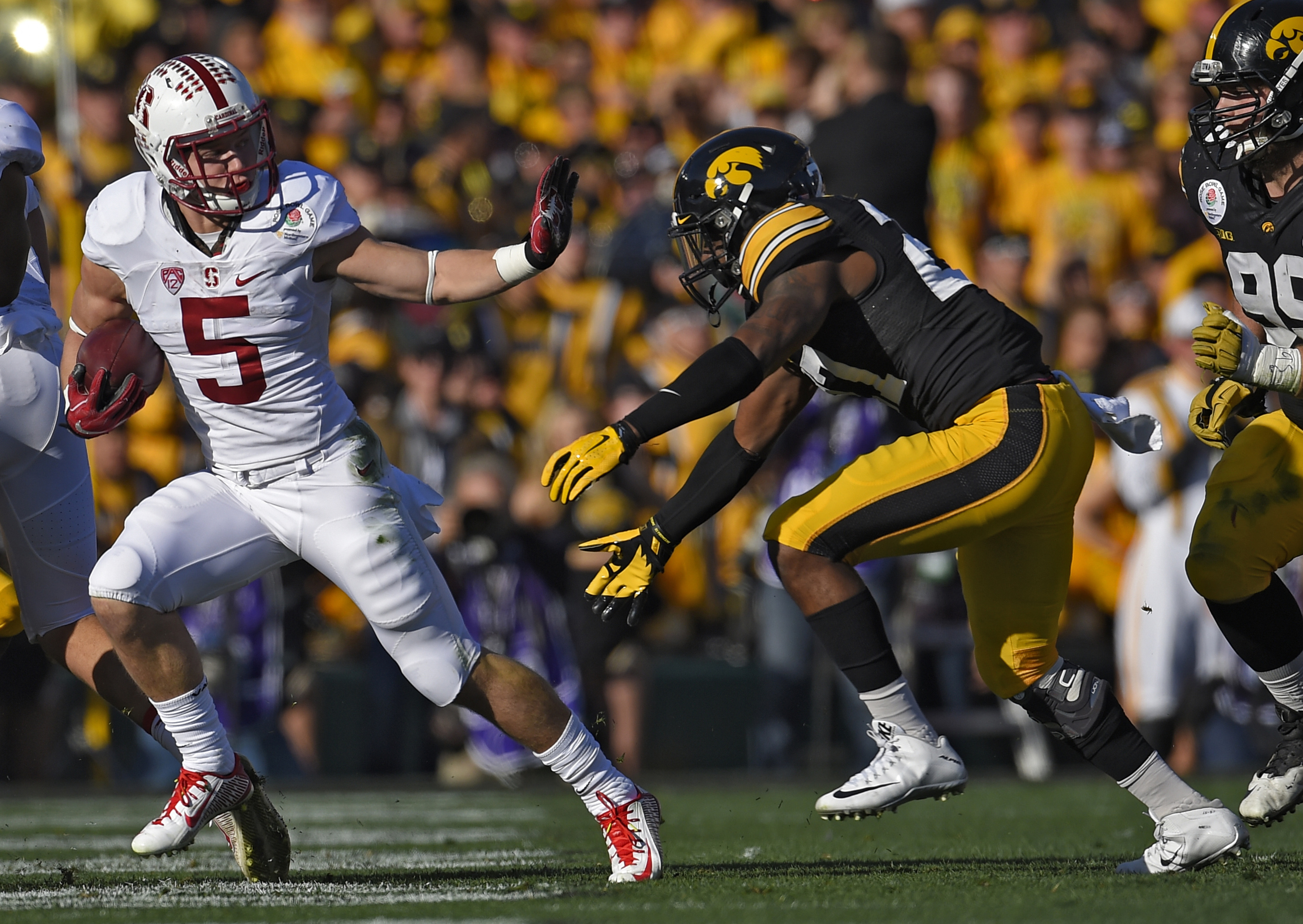 FILE - In this Jan. 1, 2016, file photo, Stanford running back Christian McCaffrey, left, runs past Iowa defensive back Jordan Lomax during the first half of the Rose Bowl NCAA college football game, in Pasadena, Calif. Now here's a scary thought for defe