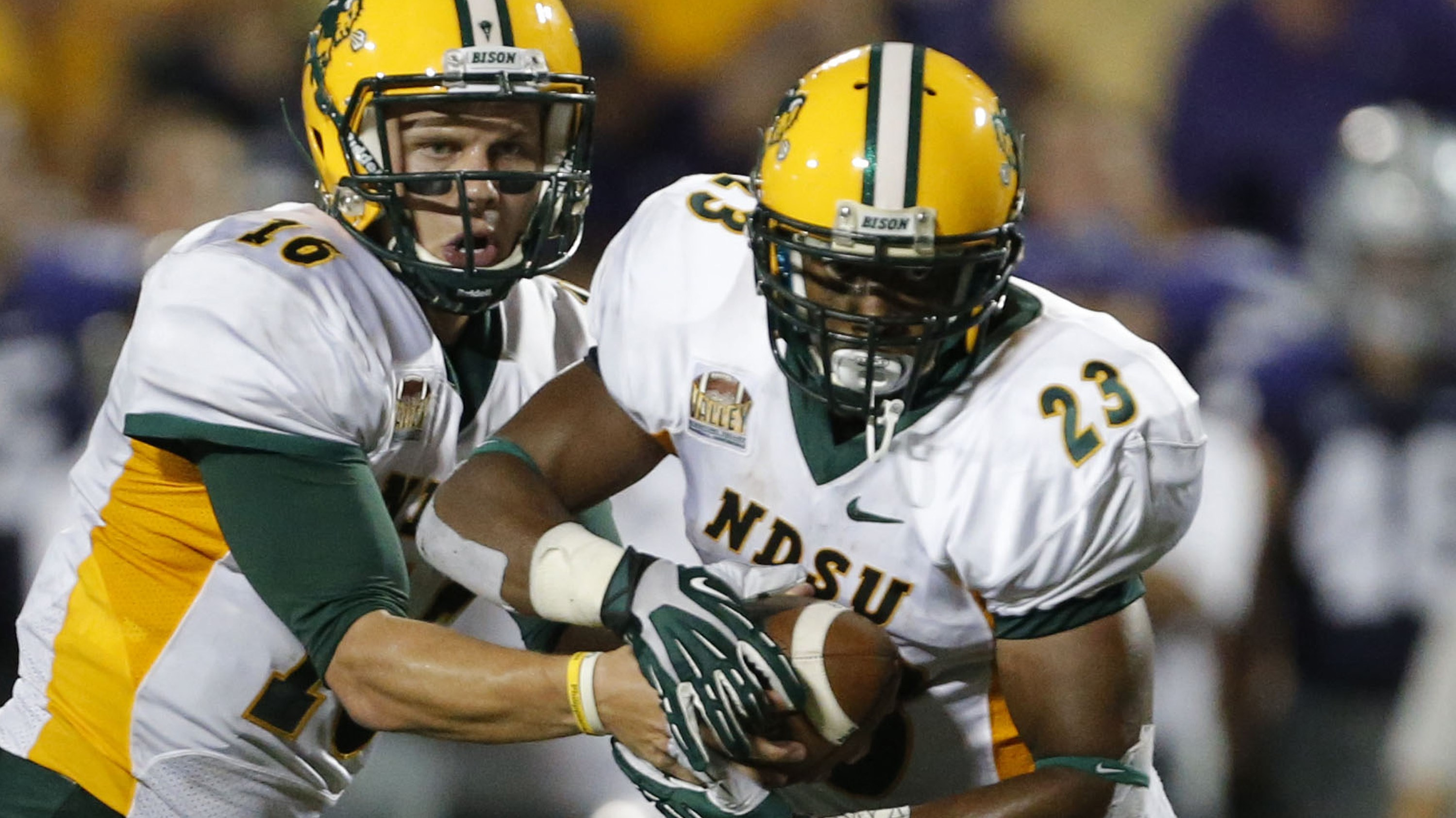 File - In this Aug. 30, 2013 file photo North Dakota State quarterback Brock Jensen (16) hands off to running back John Crockett (23) during an NCAA college football game against Kansas State in Manhattan, Kan. Crockett says hes happy that  Bison head coa