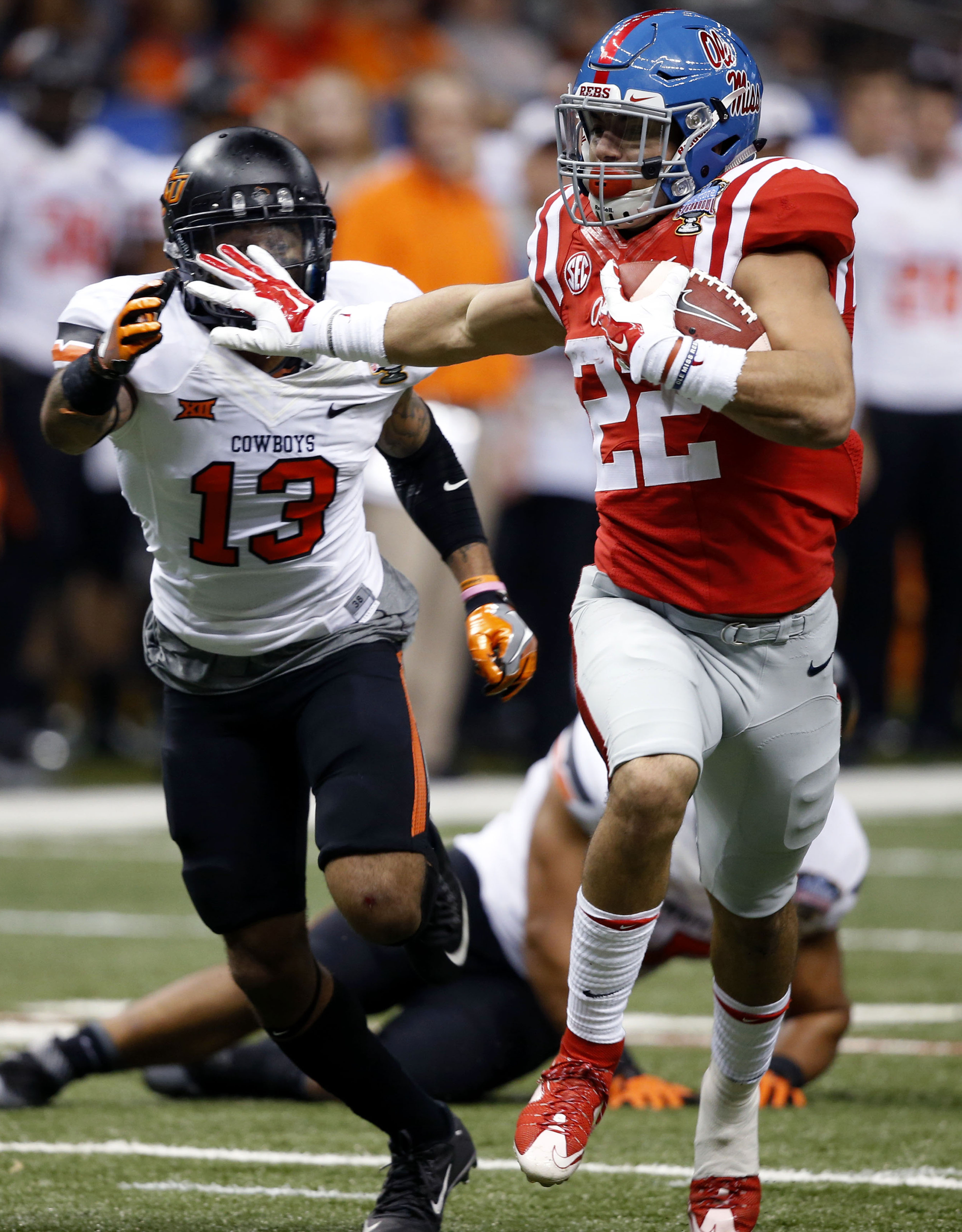 Mississippi running back Jordan Wilkins (22) carries for a touchdown as Oklahoma State safety Jordan Sterns (13) pursues in the second half of the Sugar Bowl college football game in New Orleans, Friday, Jan. 1, 2016. (AP Photo/Bill Feig)