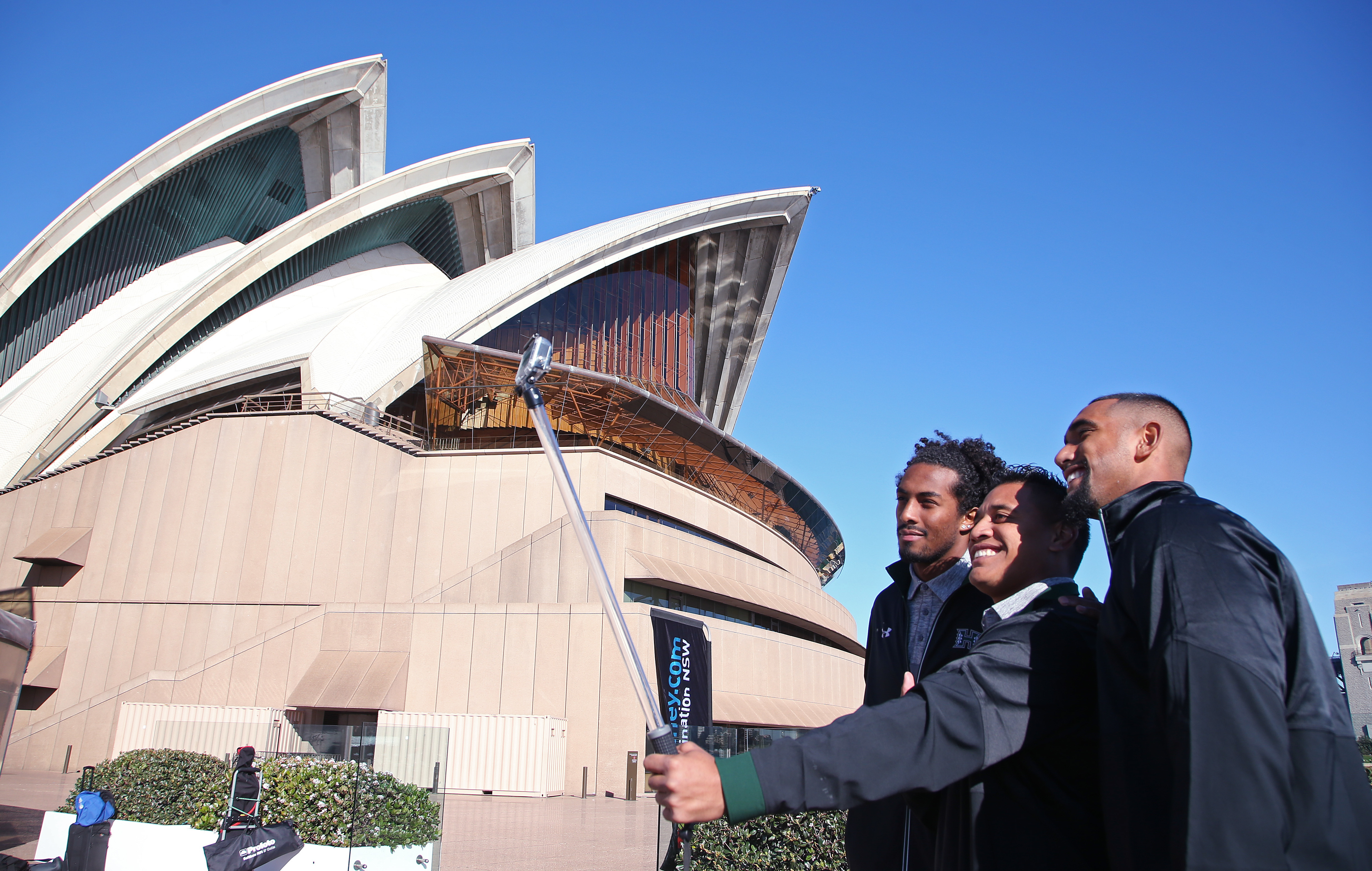 Hawaii Rainbow Warriors' players Marcus Kemp, left, Steven Lakalaka and Makan Kema-Kaleiwahia, right, take advantage of the sites around Sydney to take photos at the Opera House, Tuesday, Aug. 23, 2016, ahead of their opening college football game of the