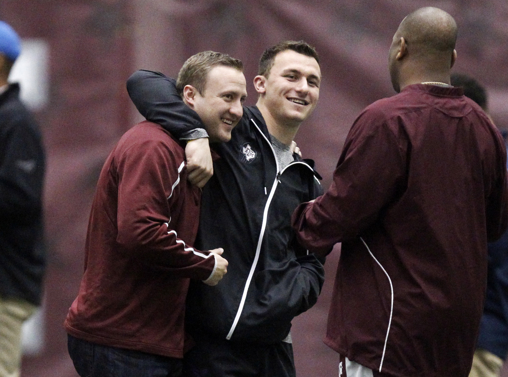 FILE - In this March 5, 2014, file photo, Texas A&M quarterback Johnny Manziel, middle, gives offensive coordinator Jake Spavital a hug during Texas A&M pro day in College Station, Texas. Spavita is now offensive coordinator with the California football t