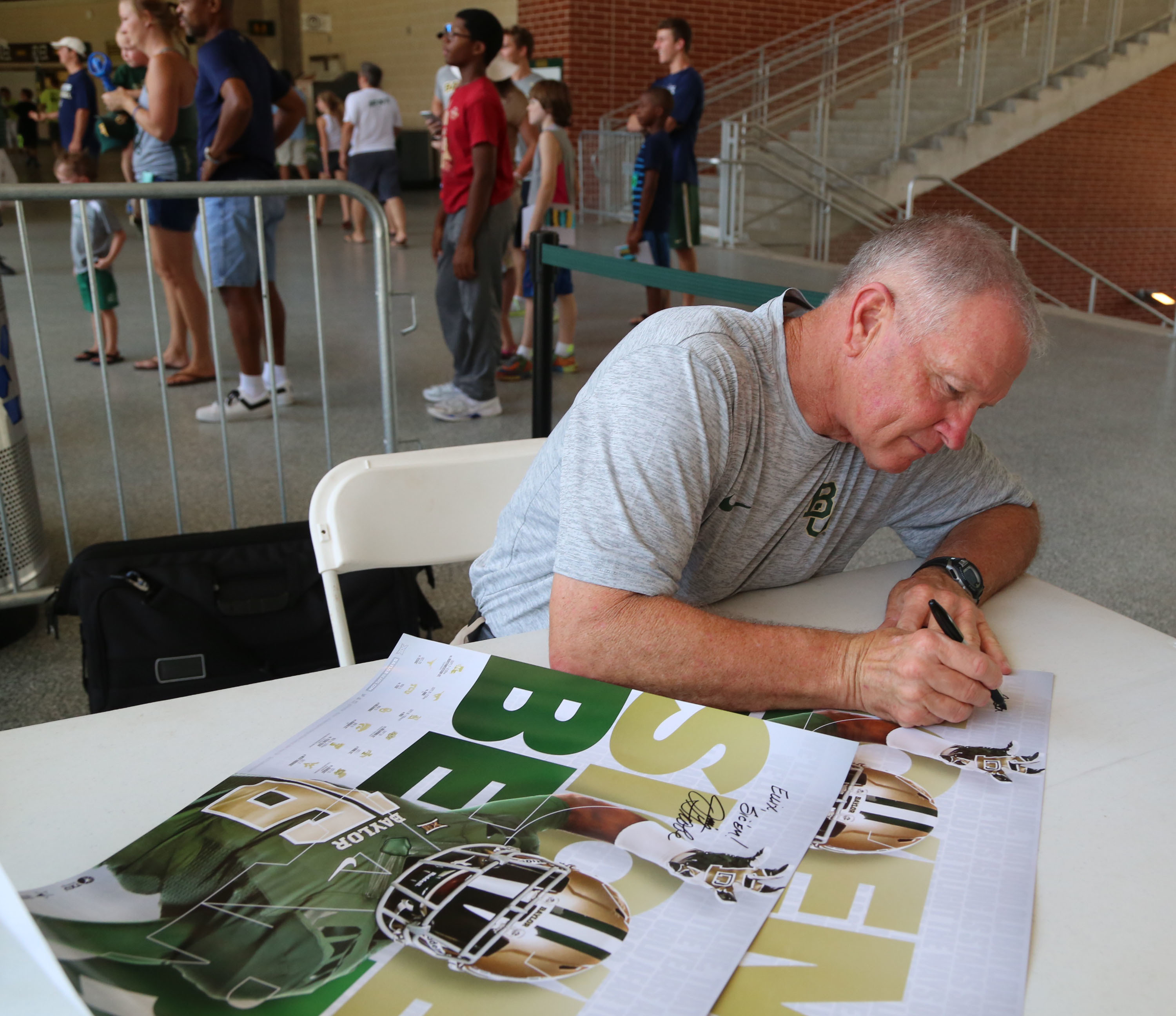 "In this Aug. 6, 2016, photo, acting head coach Jim Grobe autographs a poster during the annual ""Meet the Bear's,"" at McLane Stadium in Waco, Texas. Thousands of Baylor fans received autographs and visited with the 2016 football team. (Rod Aydelotte/Waco T"
