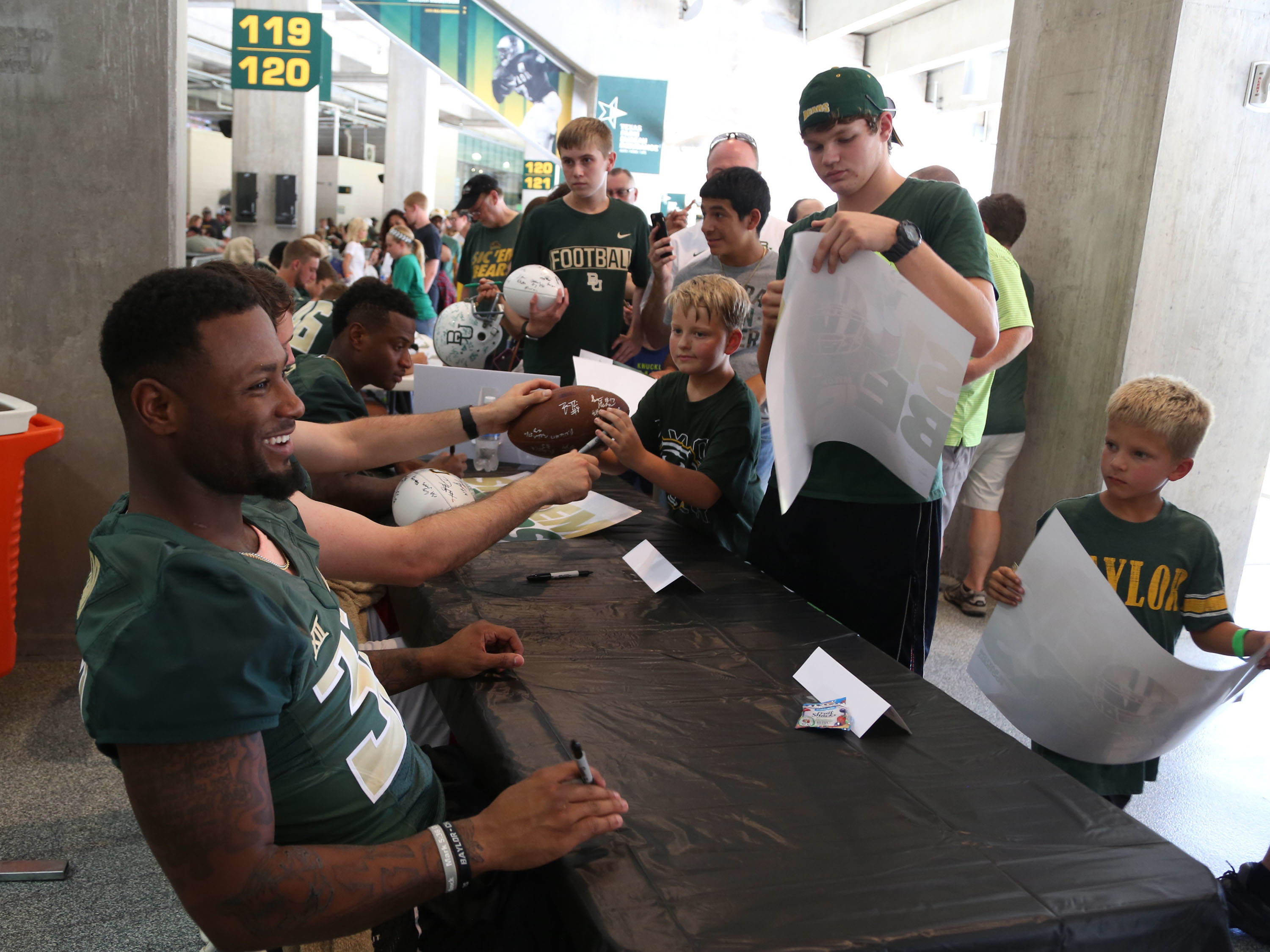 "In this Aug. 6, 2016, photo, Baylor running back Shock Linewood shares a laugh while meeting fans during the annual ""Meet the Bear's,"" at McLane Stadium in Waco, Texas. Thousands of Baylor fans received autographs and visited with the 2016 football team."