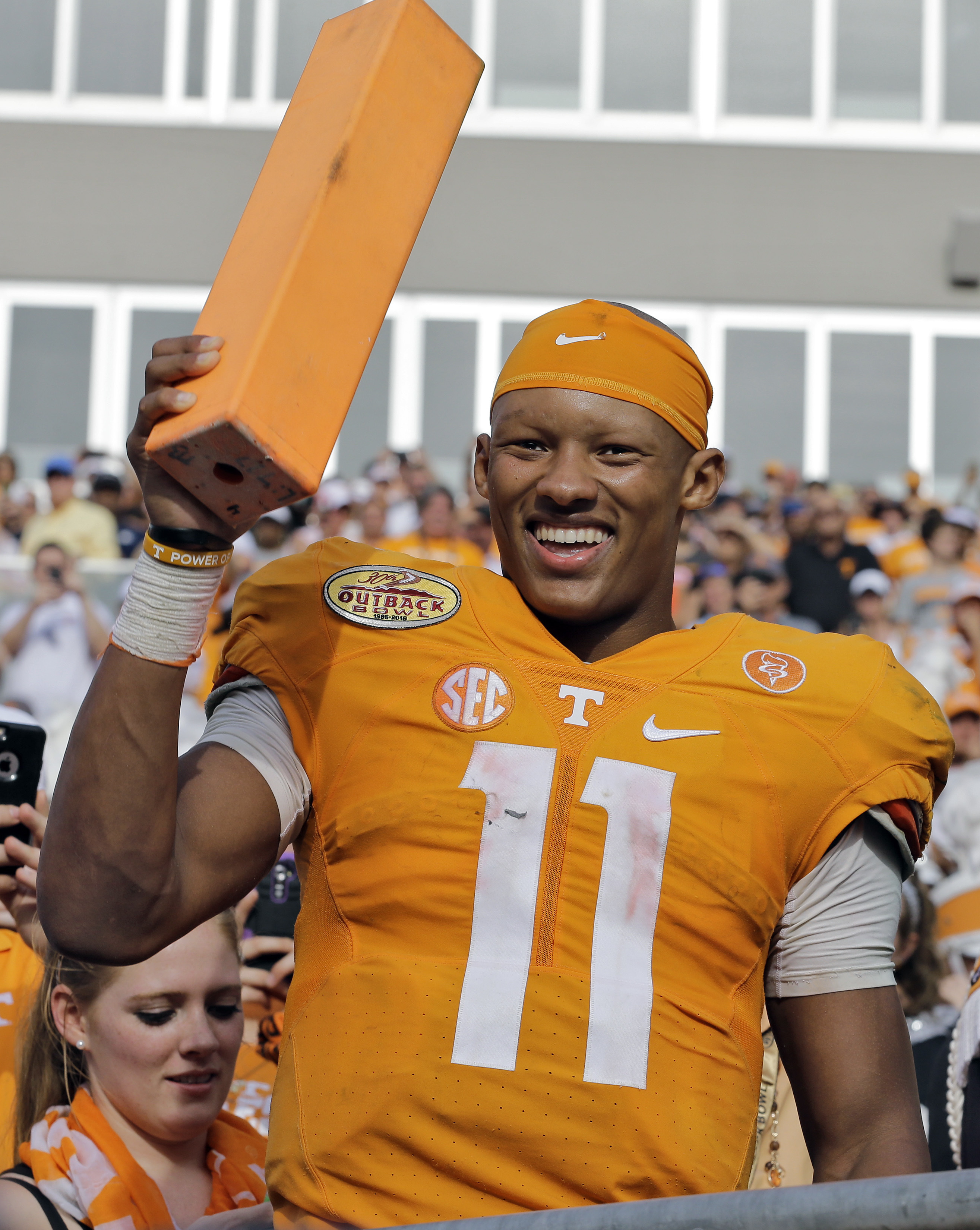 FILE - In this Jan. 1, 2016, file photo, Tennessee quarterback Joshua Dobbs smiles as he holds a pylon after their 45-6 win over Northwestern in the Outback Bowl NCAA college football game, in Tampa, Fla. Teammates and coaches say they've noticed a differ