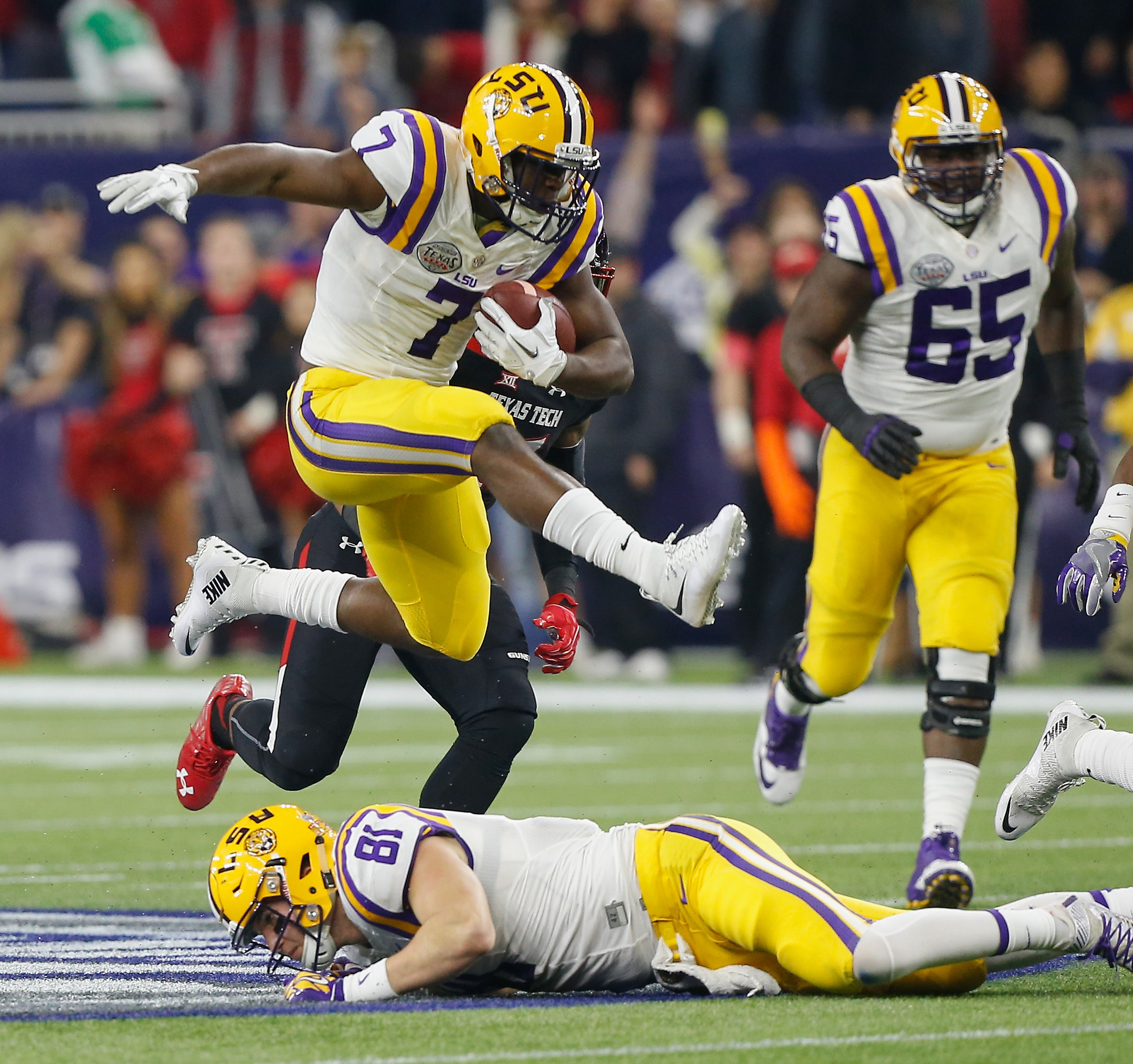 FILE - In this Dec. 29, 2015, file photo, LSU running back Leonard Fournette (7) hurdles tight end Colin Jeter (81) as he rushes against Texas Tech during the first half of the Texas Bowl NCAA college football game in Houston. All eyes are on Fournette as