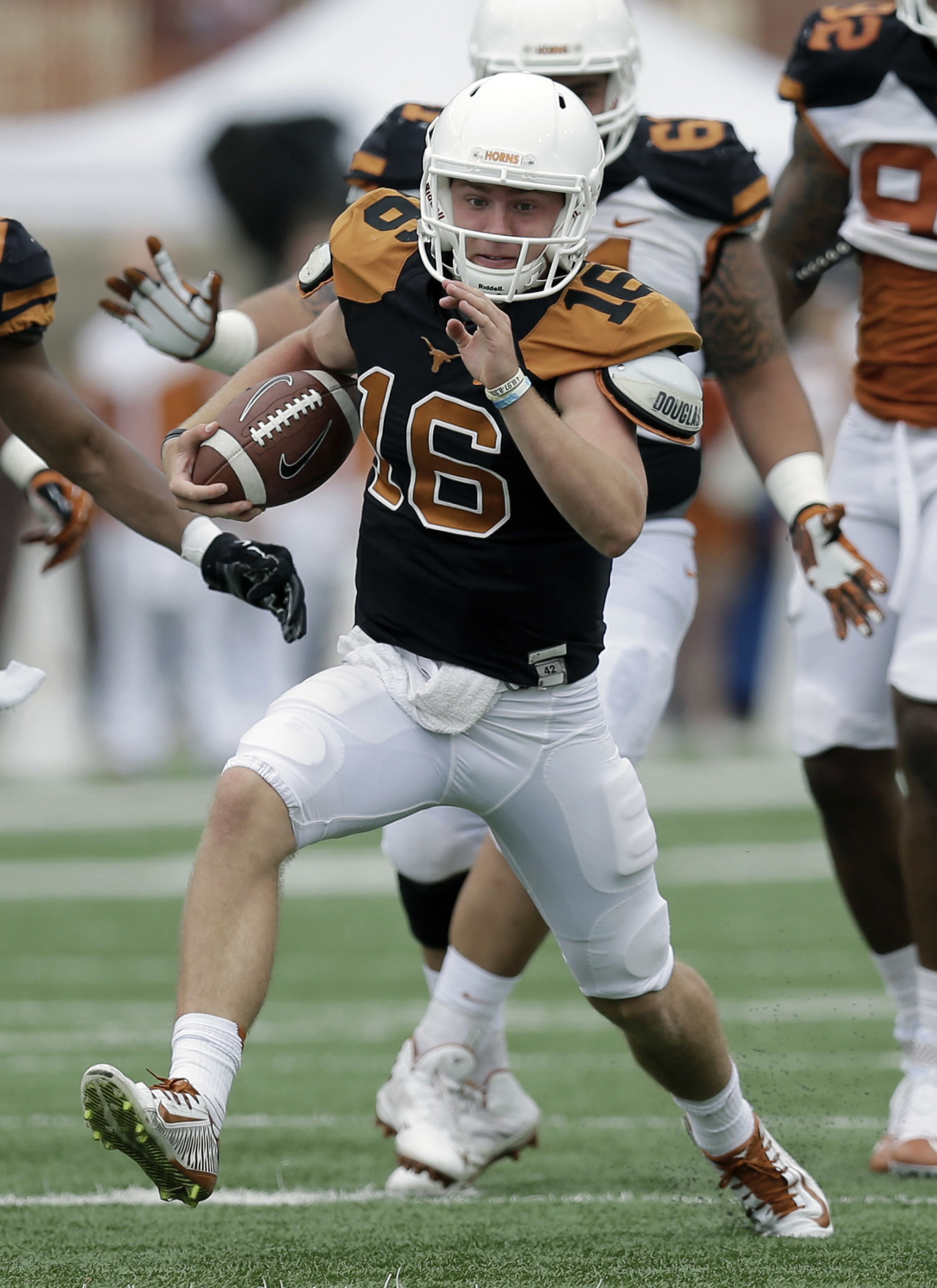 FILE - In this April 16, 2016, file photo, Texas quarterback Shane Buechele (16) scrambles for yards during a spring NCAA college football game, in Austin, Texas. Texas coach Charlie Strong is keeping his big secret until game day. Strong on Monday, Aug.