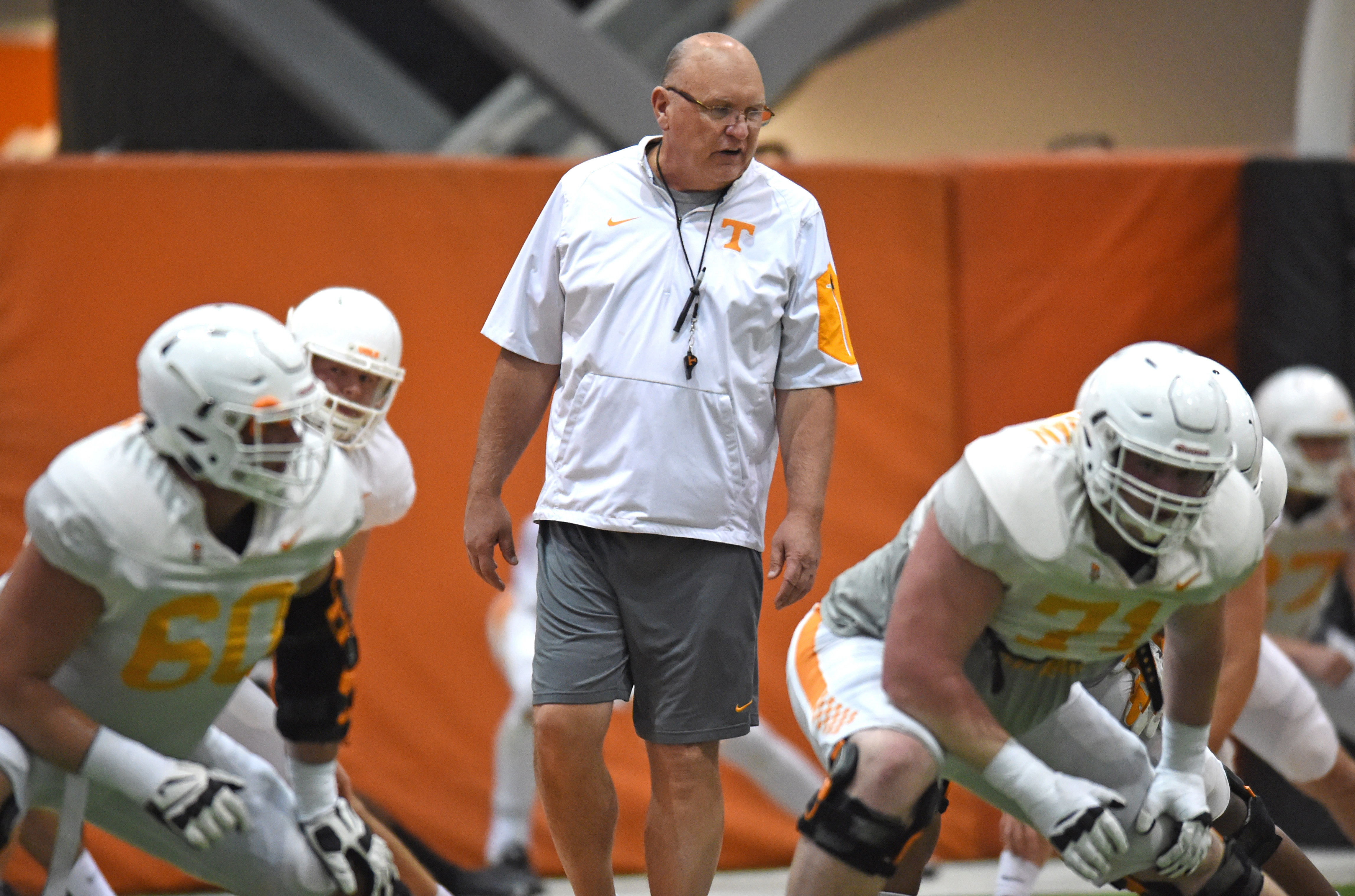 FILE -- In this March 24, 2016 file photo, Tennessee offensive coordinator Mike DeBord, center, watches as offensive linemen Austin Sanders (60) and Dylan Wiesman (71) warm up during NCAA college football practice in Knoxville, Tenn. DeBord and defensive