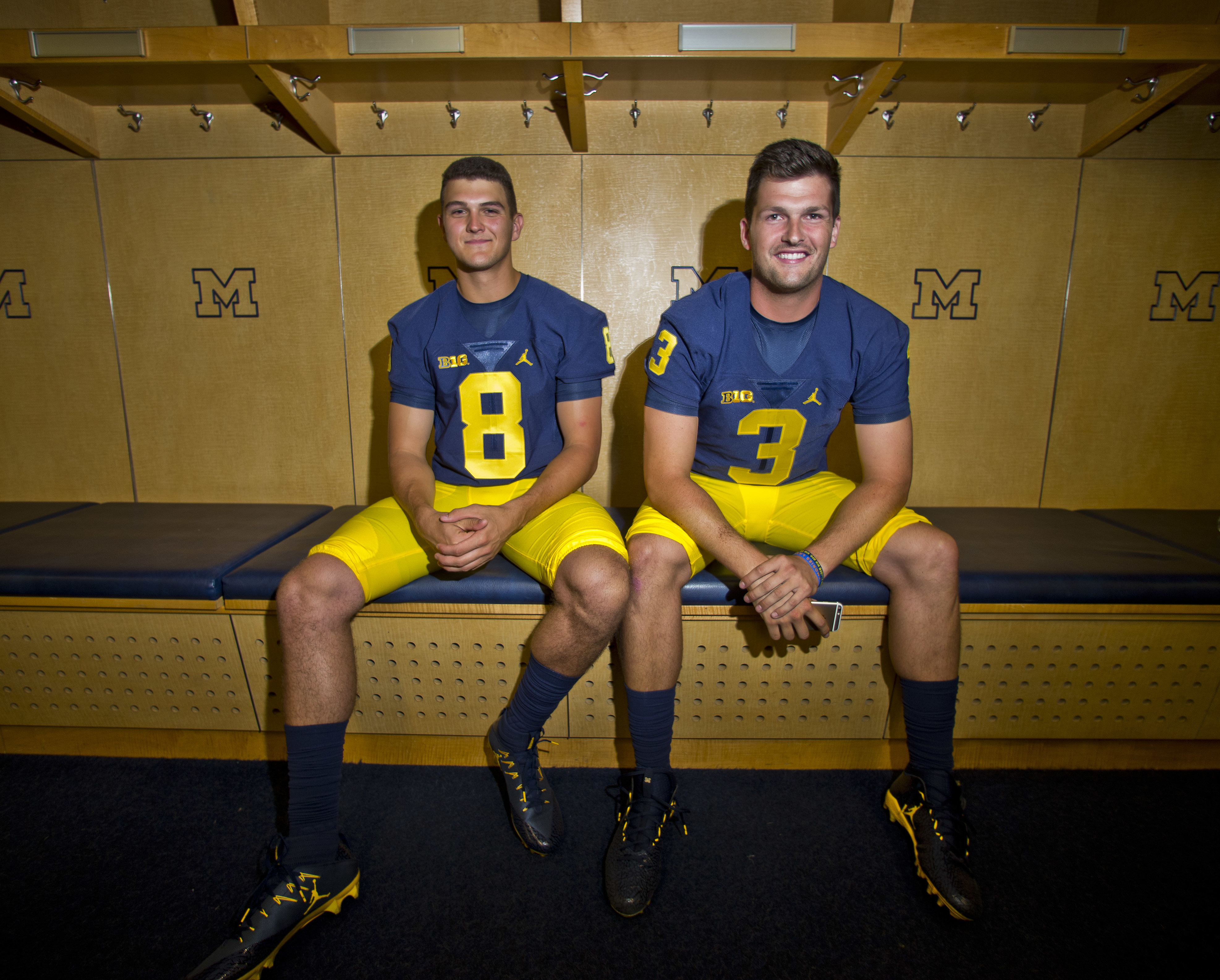 FILE - This Aug. 7, 2016 file photo shows Michigan quarterbacks John O'Korn (8) and Wilton Speight (3) sitting for a photo in the locker room during the NCAA college football team's preseason media day at Michigan Stadium in Ann Arbor, Mich. Jim Harbaugh