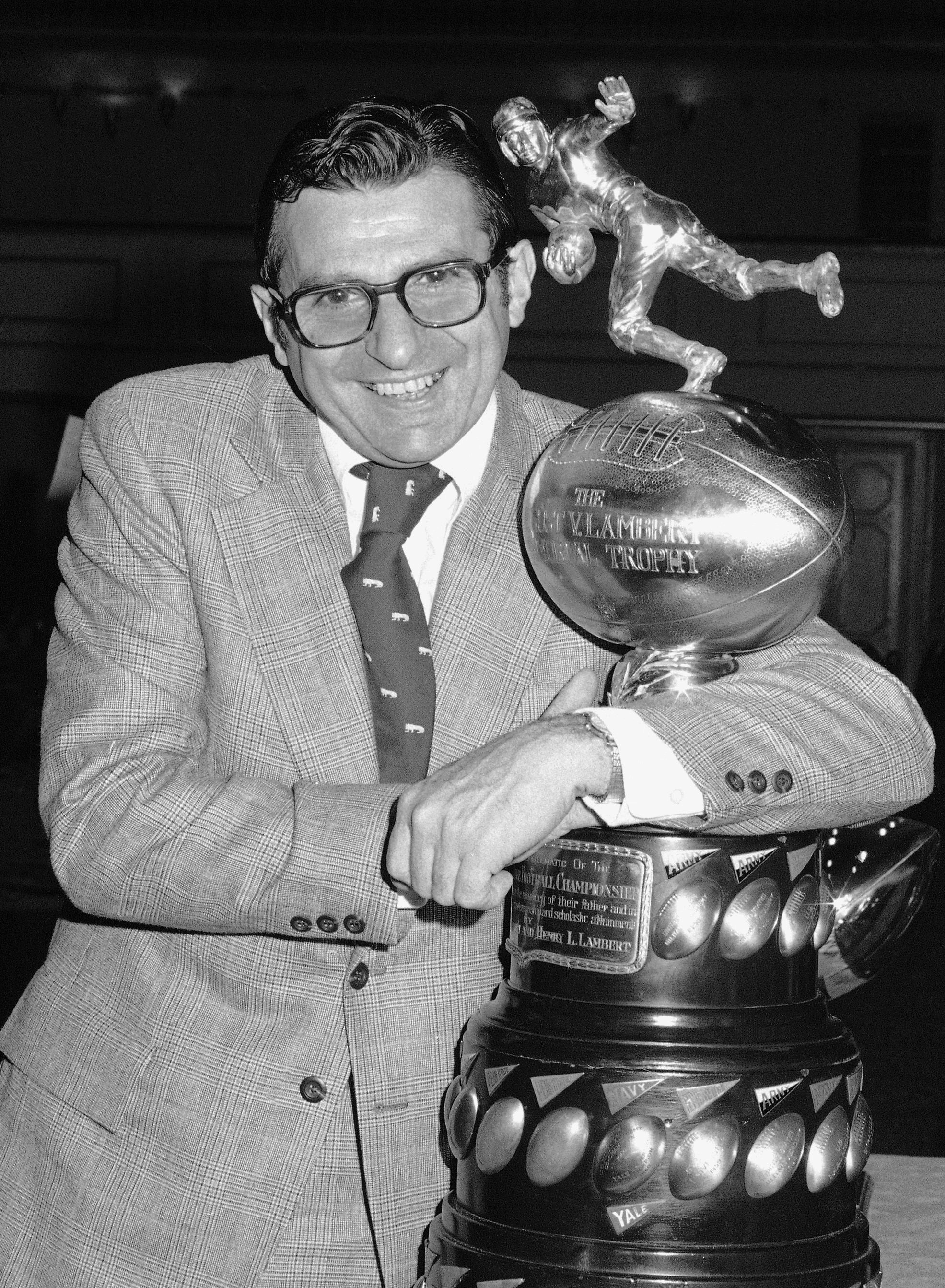 FILE - In this Dec. 6, 1973, file photo, Joe Paterno, head coach of the Penn State football team, clutches the Lambert Trophy in New York, after it was awarded to his team as emblematic of collegiate grid supremacy in the East. Legends tend to linger in c
