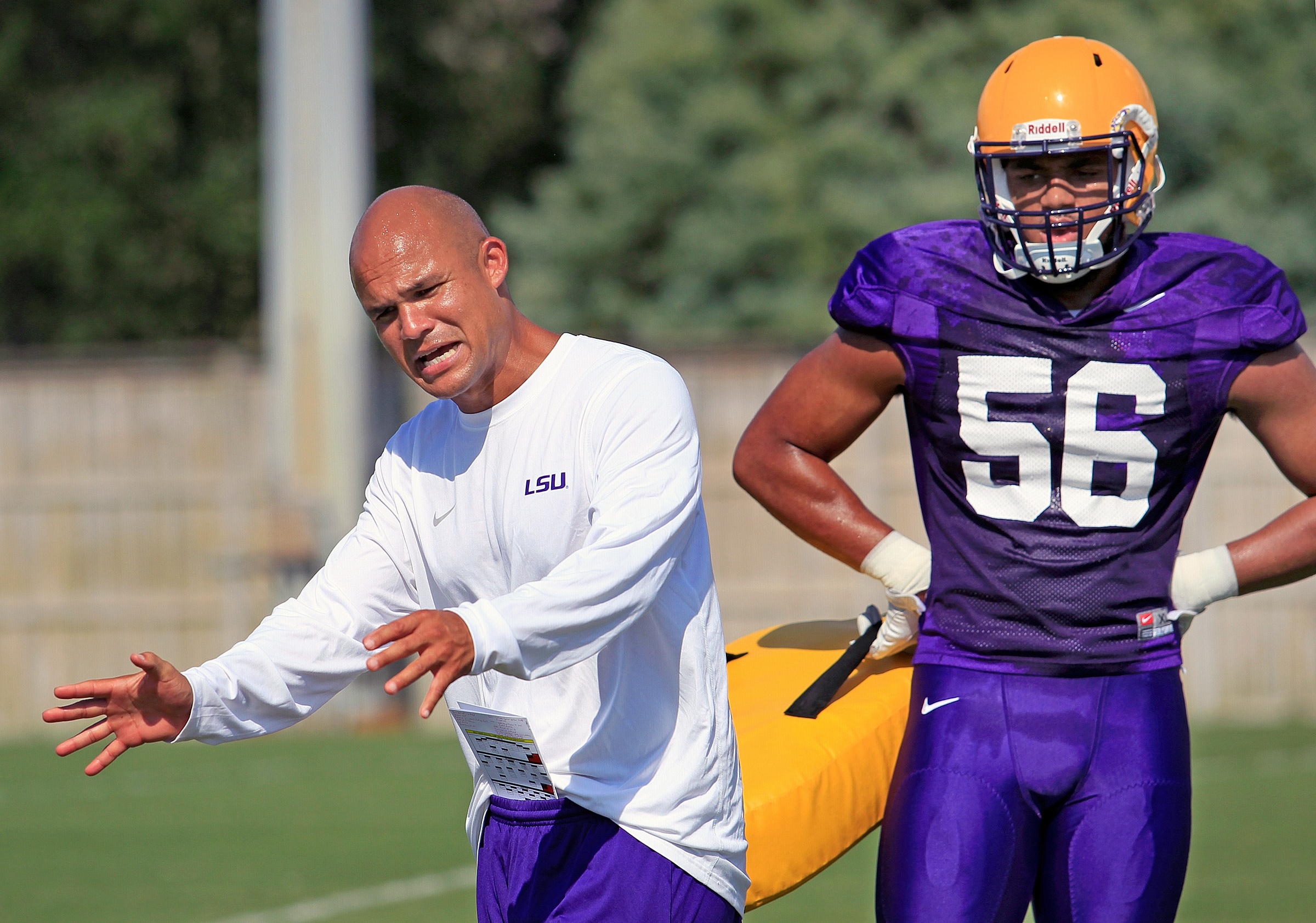 In this Aug. 6, 2016, photo, LSU defensive coordinator Dave Aranda gives instructions to Tigers M.J. Patterson during an NCAA college football practice in Baton Rouge, La.  Wisconsin's marquee season opener on Saturday against No. 5 LSU features a unique