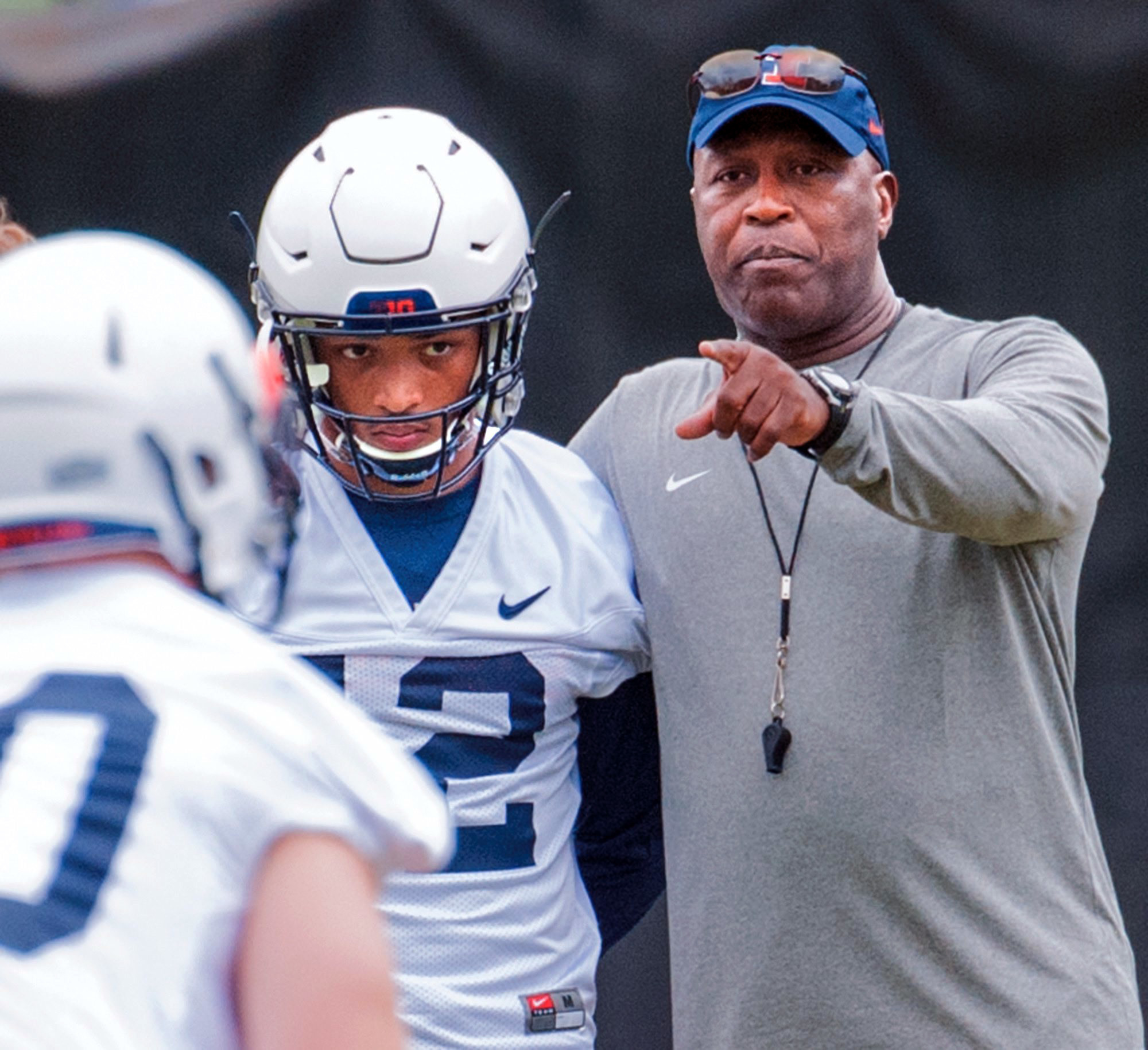 In this Aug. 5, 2016 photo, Illinois head football coach Lovie Smith chats with defensive back Chris James during NCAA college football practice at Memorial Stadium in Champaign, Ill. The Illini are adapting to the defensive philosophy their new coach Smi