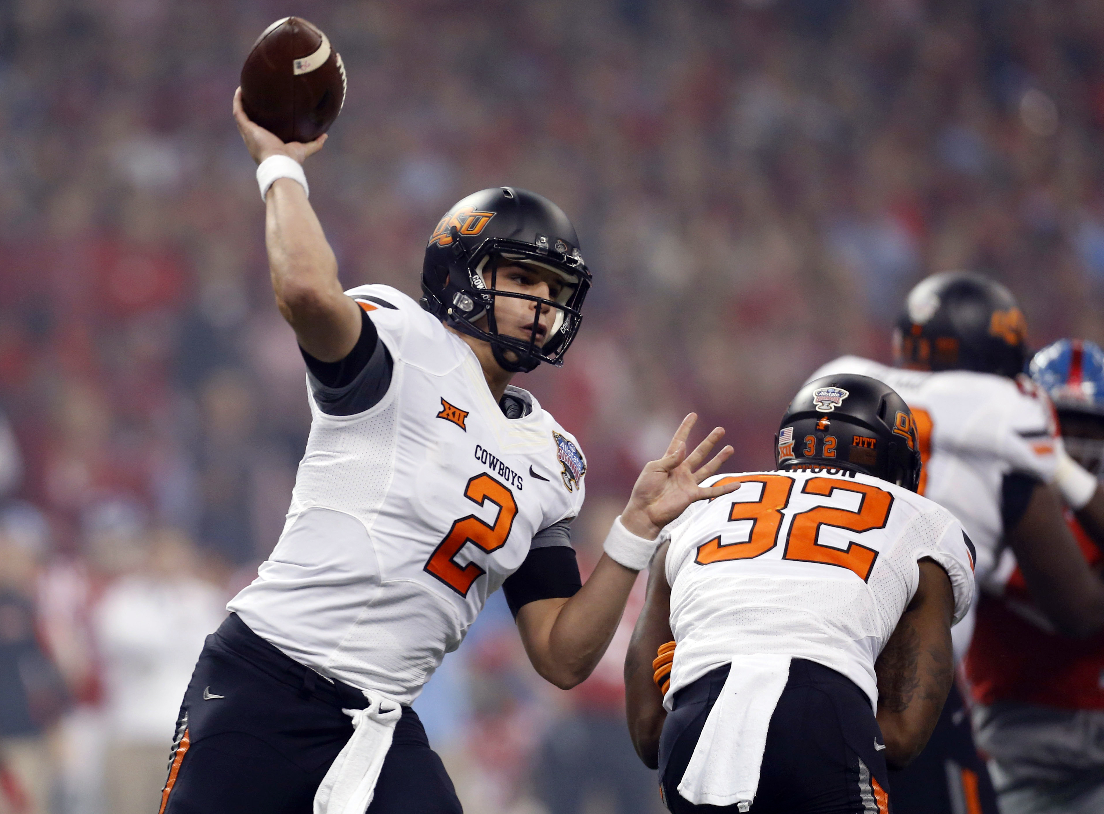 FILE - In this Jan. 1, 2016 file photo, Oklahoma State quarterback Mason Rudolph throws a pass durring the first half of the Sugar Bowl college football game in New Orleans. Rudolph heads into his junior year with a plethora of weapons around him and high