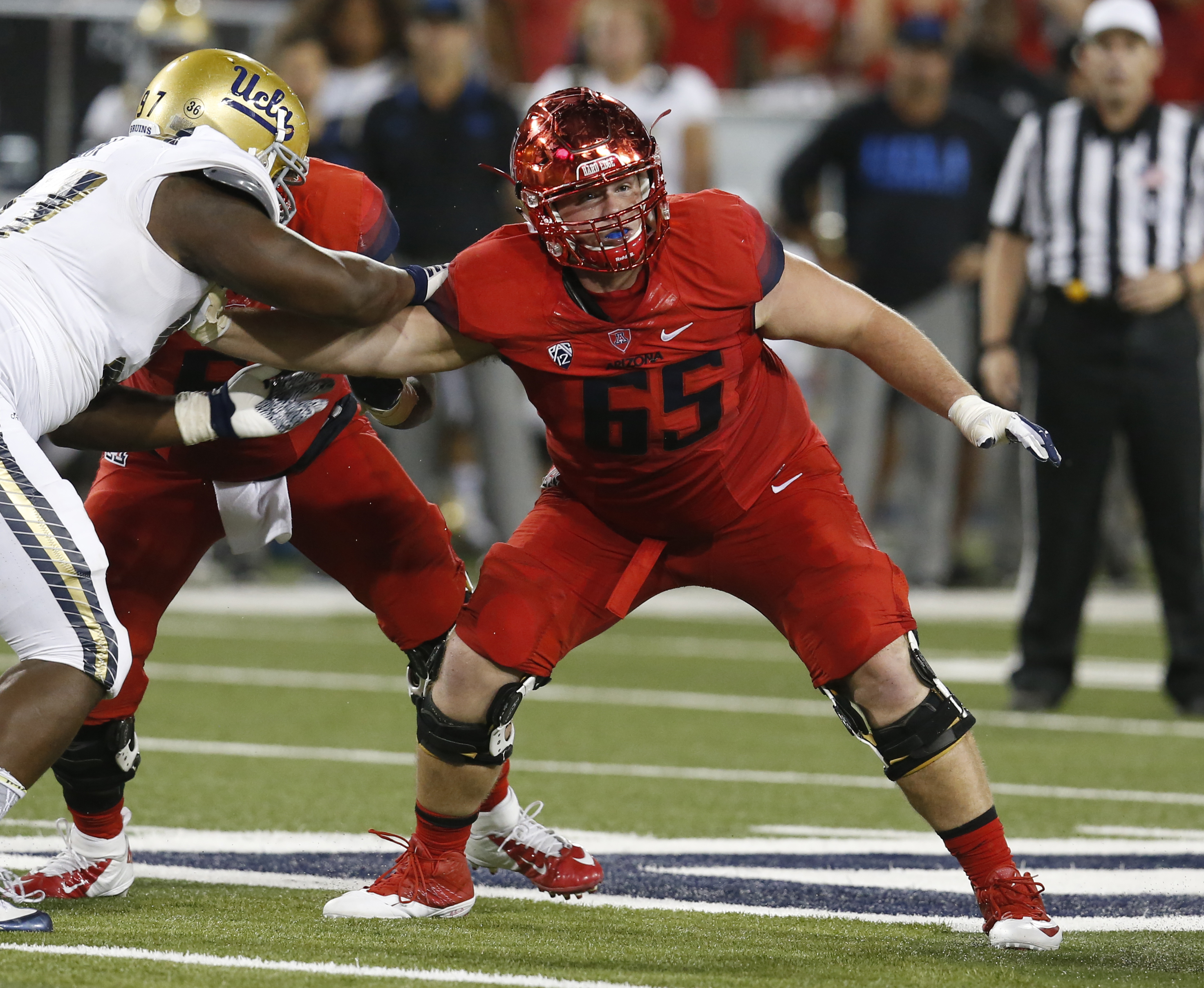 FILE - In this Sept. 26, 2015, file photo, Arizona offensive lineman Zach Hemmila (65) blocks a UCLA player during the first half of an NCAA college football game in Tucson, Ariz. Arizona had to endure one of the most difficult fall camps anywhere, trying