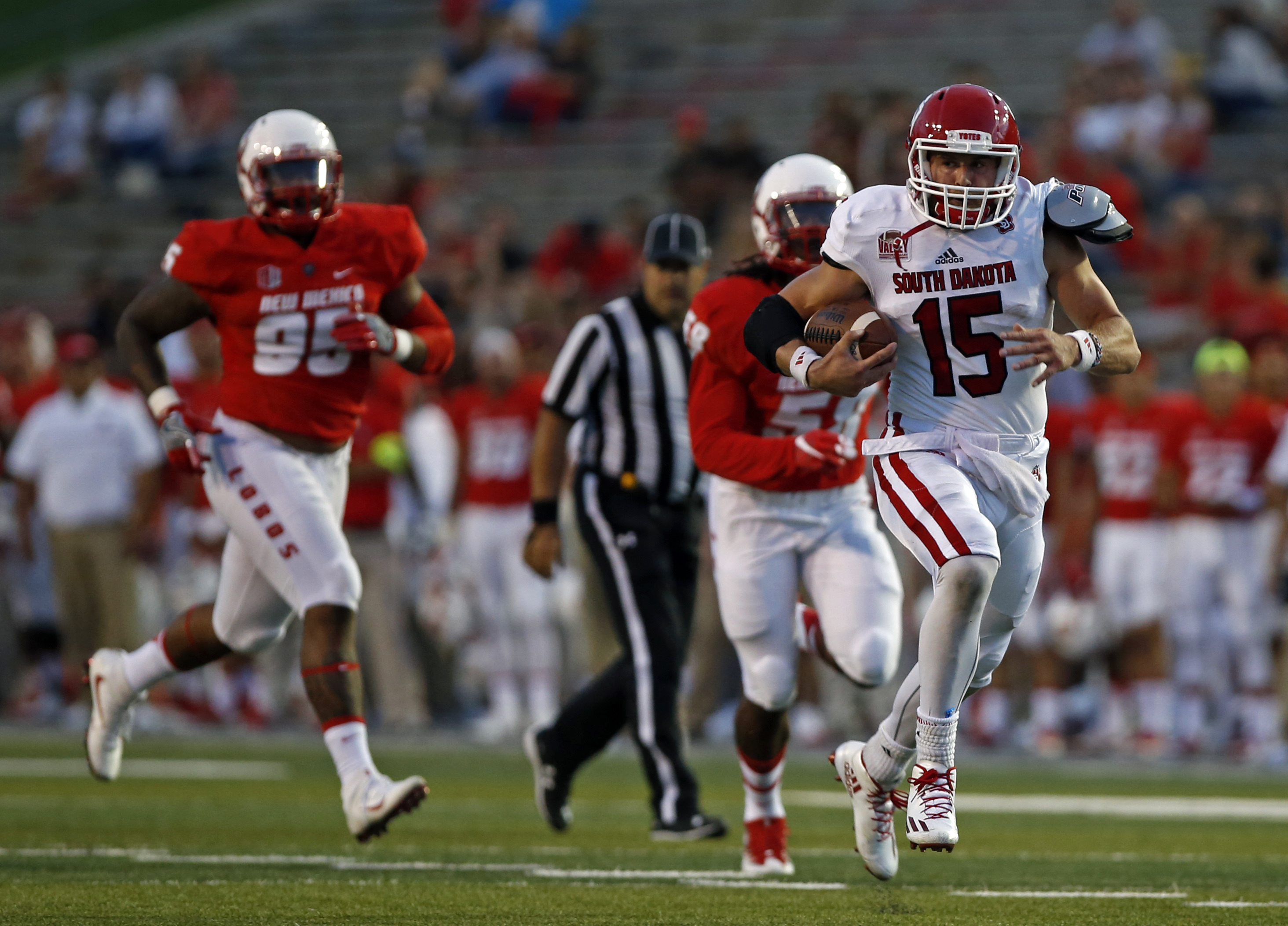 South Dakota quarterback Chris Streveler (15) sprints to the end zone for a touchdown ahead of New Mexico defensive lineman Garrett Hughes (95) and linebacker Maurice Daniels (58) during the first half of an NCAA college football game in Albuquerque, N.M.
