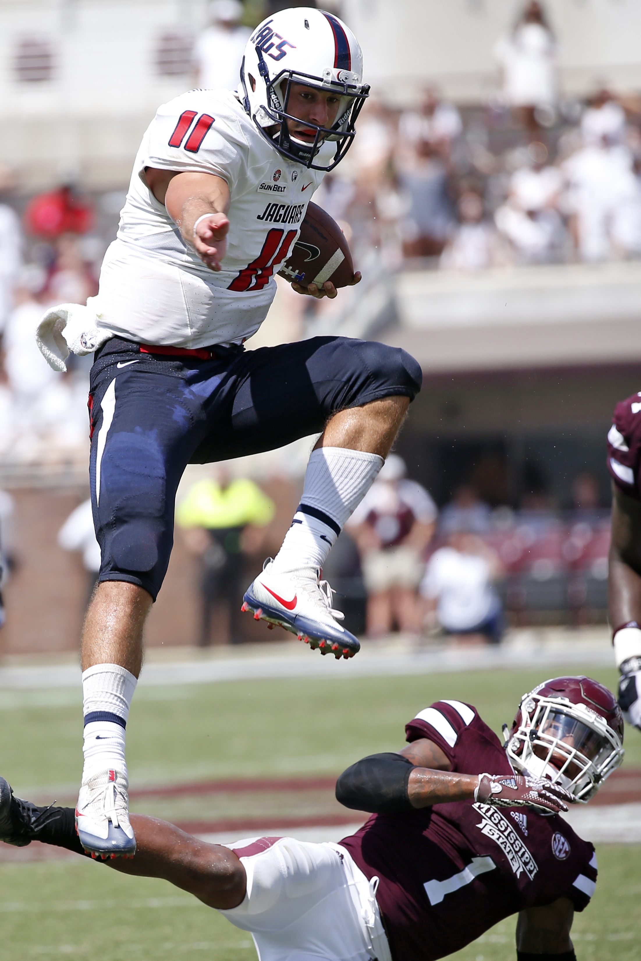 South Alabama quarterback Dallas Davis (11) leaps over Mississippi State defensive back Brandon Bryant (1) on a short run in the second half of an NCAA college football game in Starkville, Miss., Saturday, Sept. 3, 2016. South Alabama won 21-20. (AP Photo