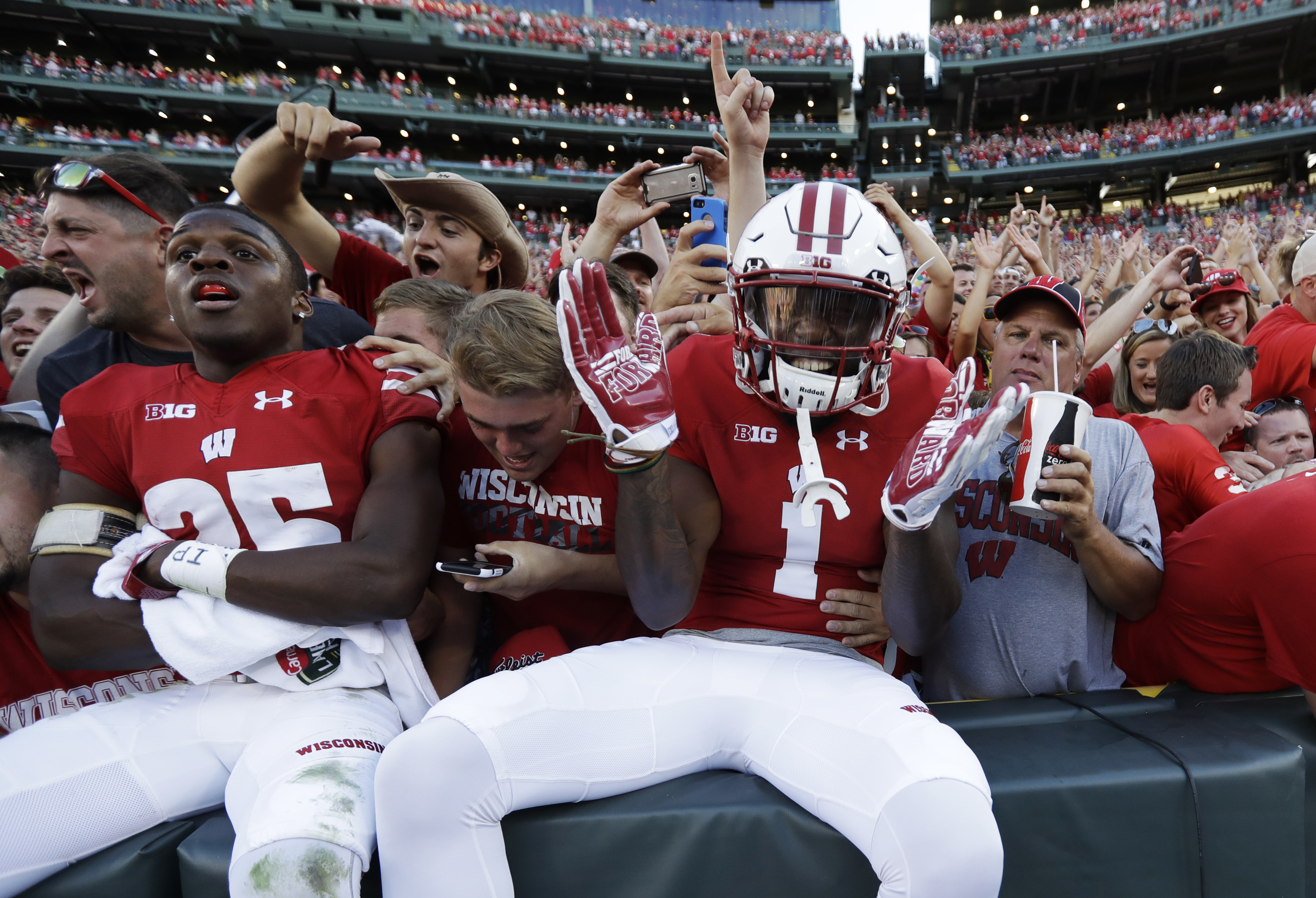 Wisconsin's Reggie Love (1) and Derrick Tindal (25) celebrate with fans after an NCAA college football game against LSU Saturday, Sept. 3, 2016, in Green Bay, Wis. Wisconsin won 16-14. (AP Photo/Morry Gash)