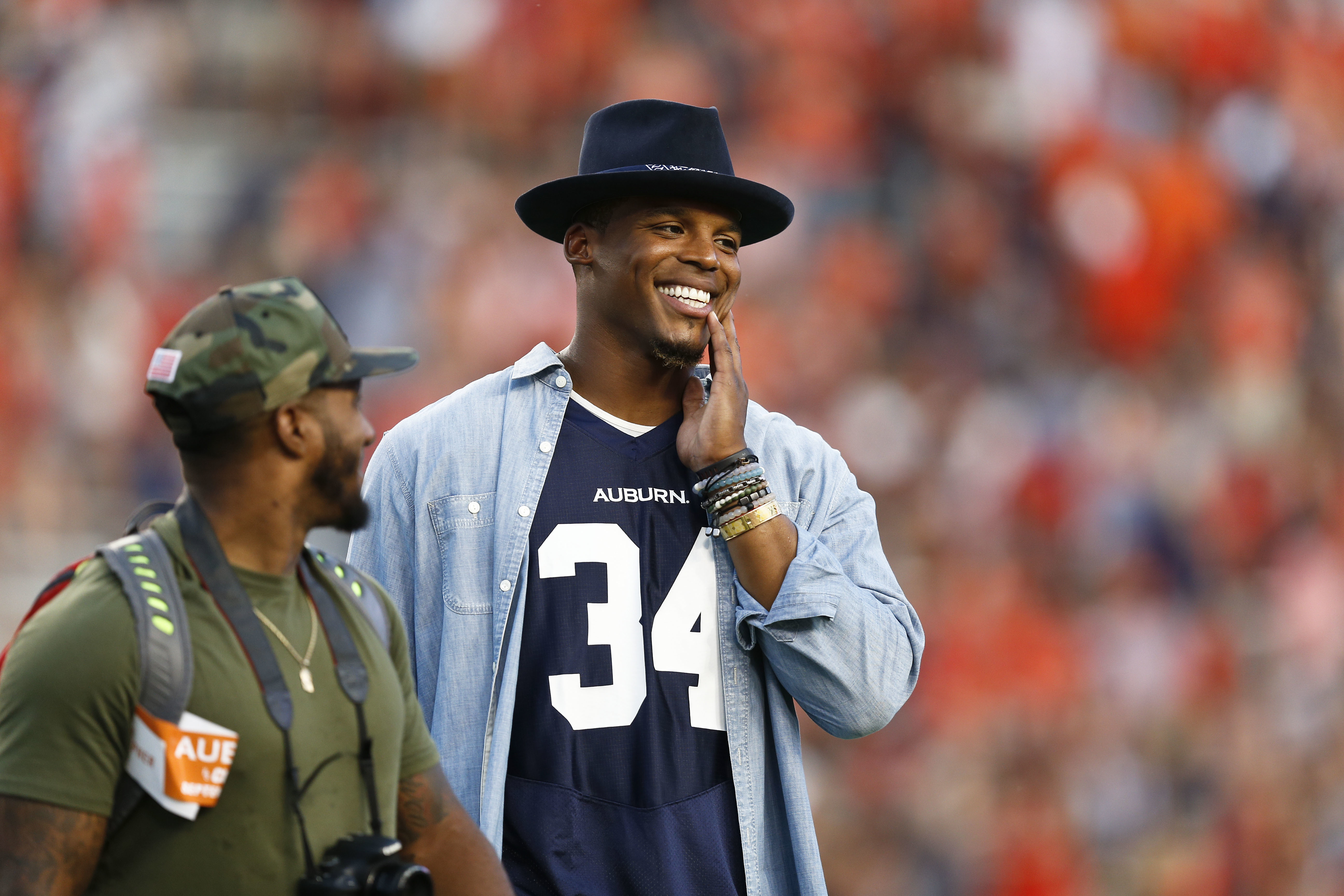 Carolina Panthers quarterback Cam Newton smiles as he watches Auburn and Clemson players warm up for an NCAA college football game, Saturday, Sept. 3, 2016, in Auburn, Ala. (AP Photo/Brynn Anderson)
