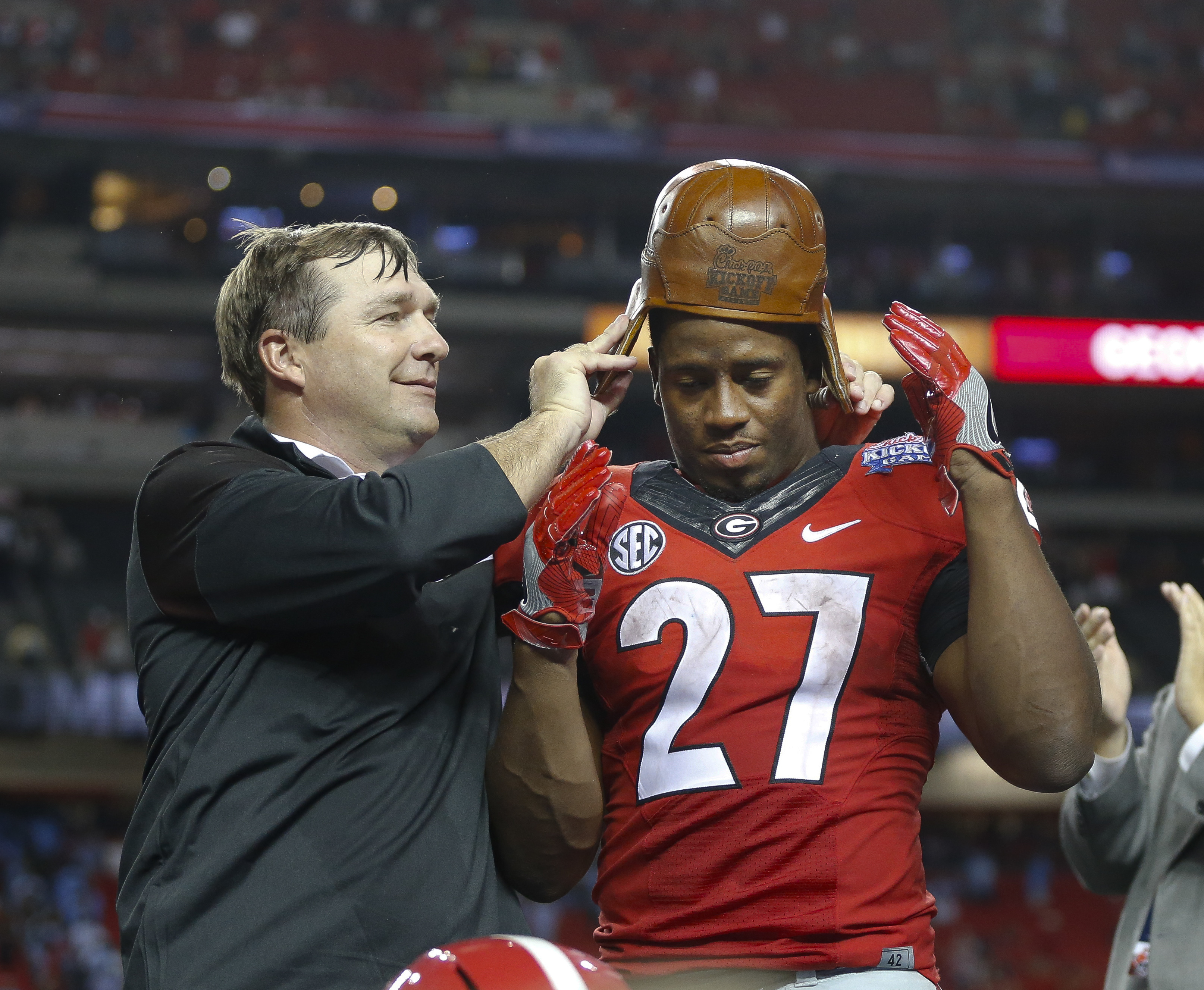 """Georgia head coach Kirby Smart puts the """"Old Leather Helmet"""" on running back Nick Chubb's head after an NCAA college football game against North Carolina in Atlanta, Saturday, Sept. 3, 2016. Georgia won 33-24. The helmet is part of a trophy awarded to the"""