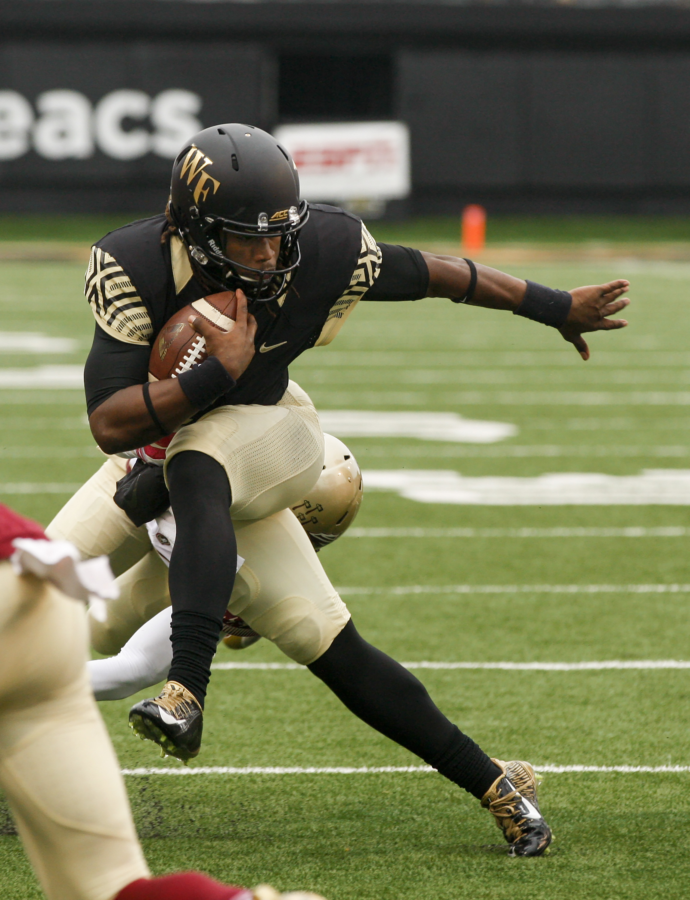 FILE - In this Oct. 3, 2015, file photo, Wake Forest quarterback Kendall Hinton tries to break a tackle as he carries the ball against Florida State in the first half of an NCAA college football game in Winston-Salem, N.C. Duke has handed the offense over