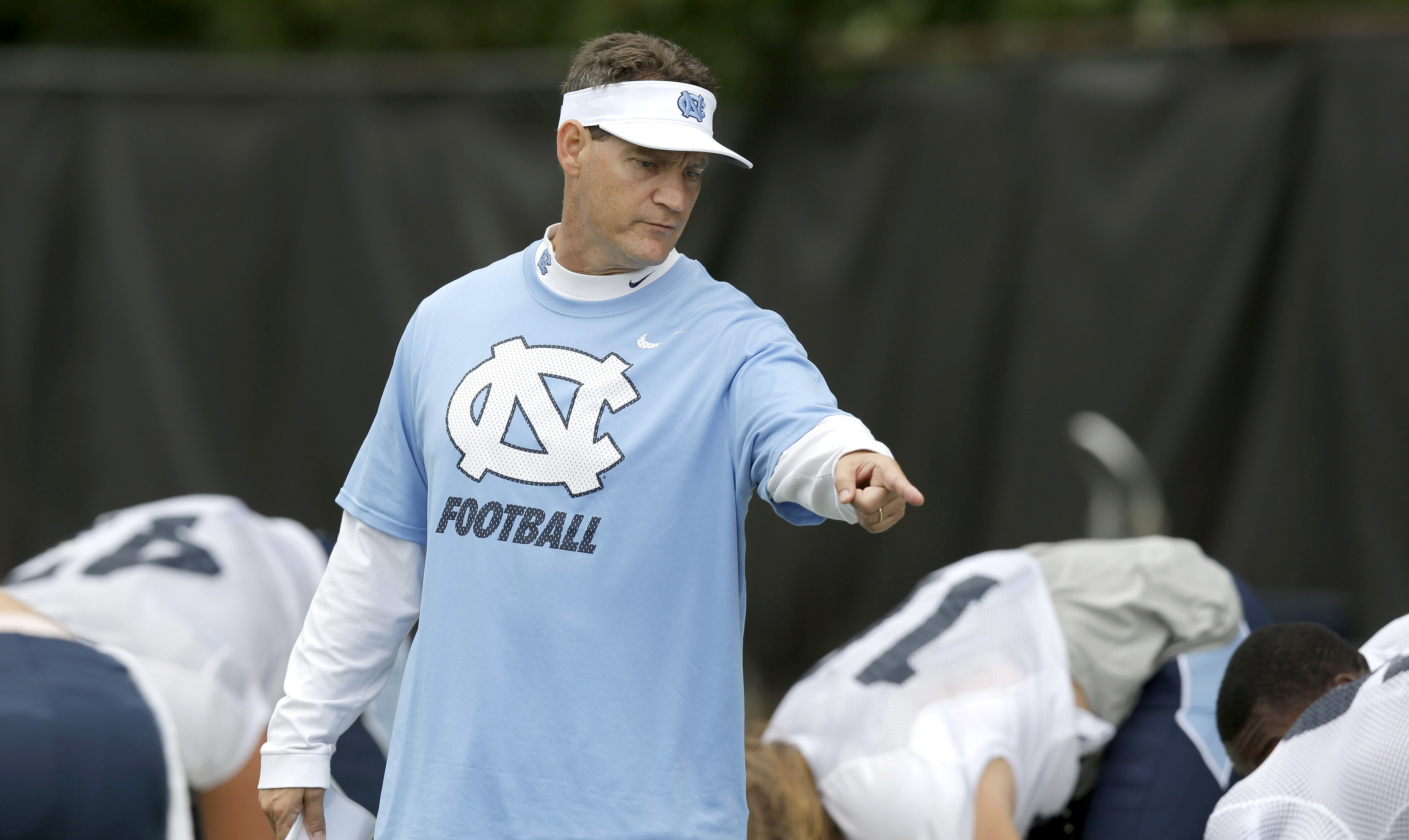 FILE - In this Aug. 10, 2015, file photo, North Carolina defensive coordinator Gene Chizik works with players during an NCAA college football practice in Chapel Hill, N.C. Chizik said it's difficult for defenses to prepare when they face so many new offen