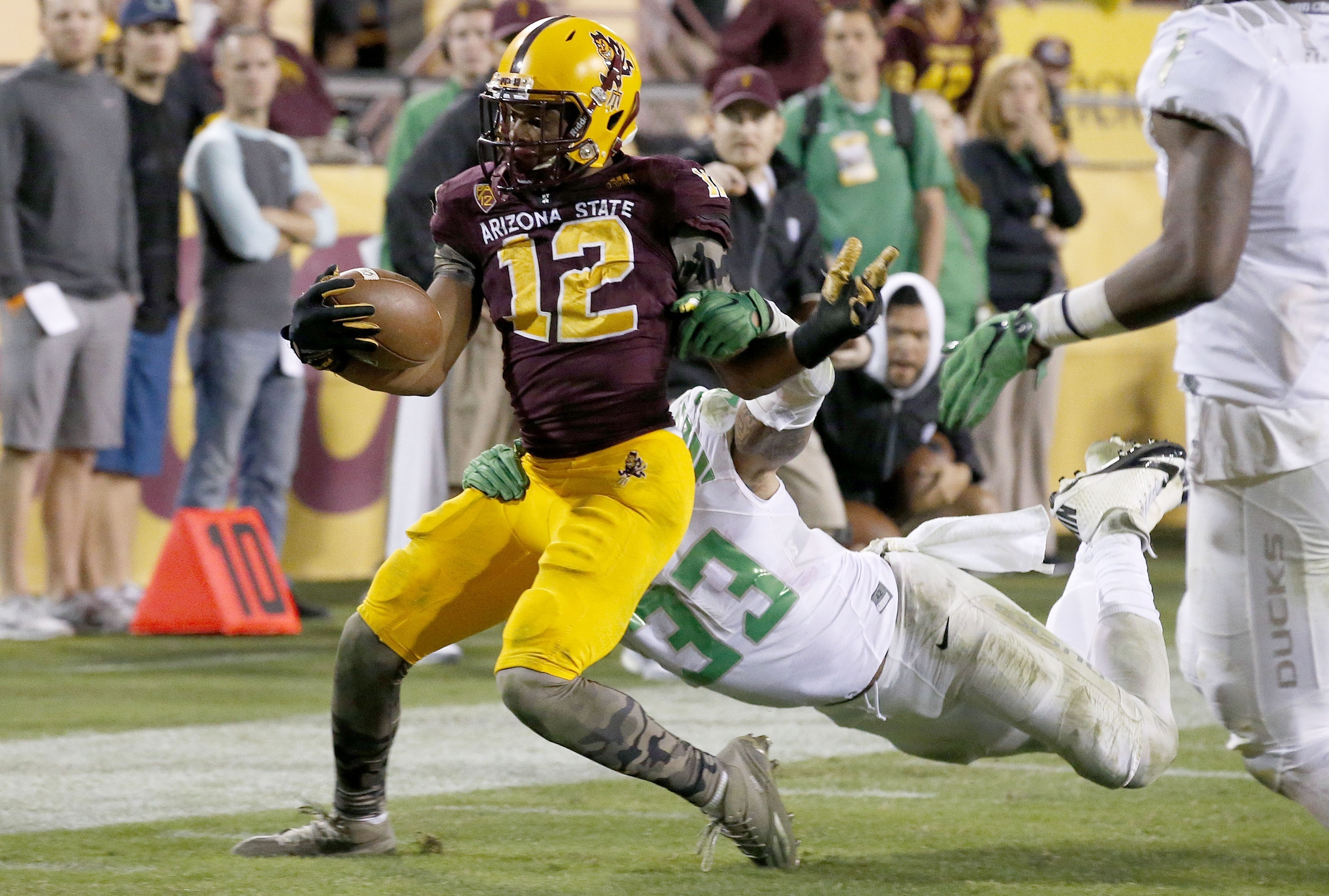 FILE - In this Oct. 29, 2015, file photo, Arizona State's Tim White (12) is able to shed the tackle of Oregon's Tyson Coleman (33) just enough to get into the end zone for a touchdown during overtime of an NCAA college football game in Tempe, Ariz. ASU ho