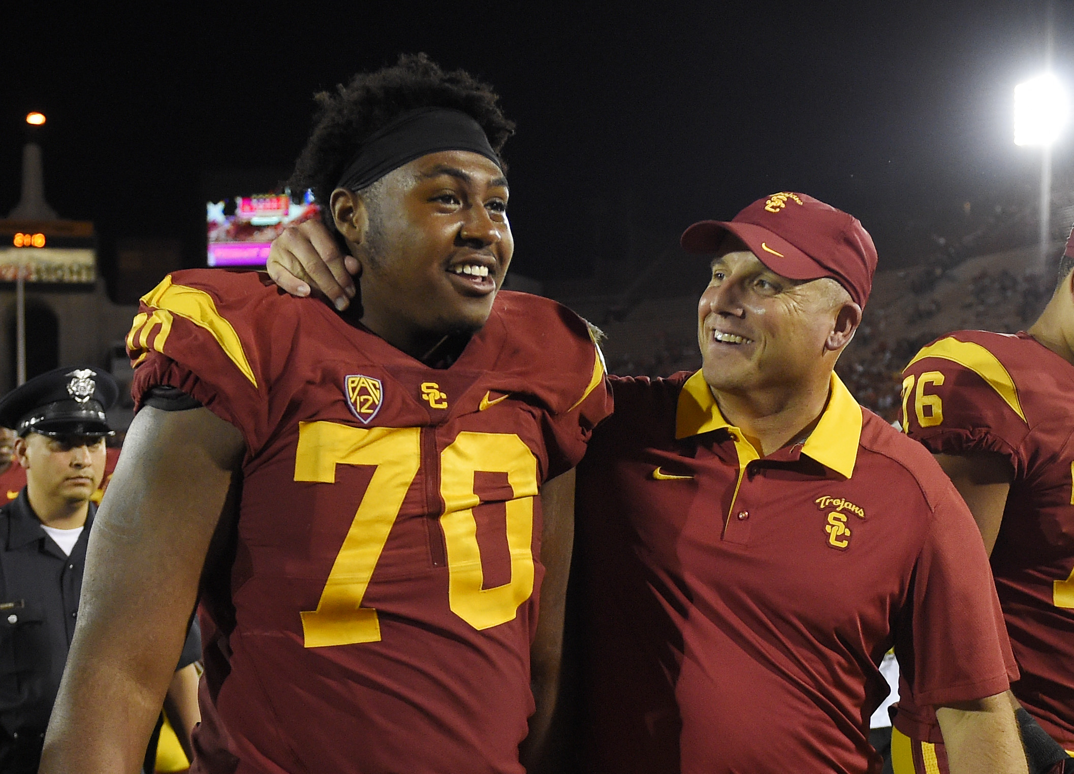 Southern California interim head coach Clay Helton, right, puts his arm around Southern California offensive tackle Chuma Edoga as they walk off the field after USC defeated Utah 42-24 in a NCAA college football game, Saturday, Oct. 24, 2015, in Los Angel