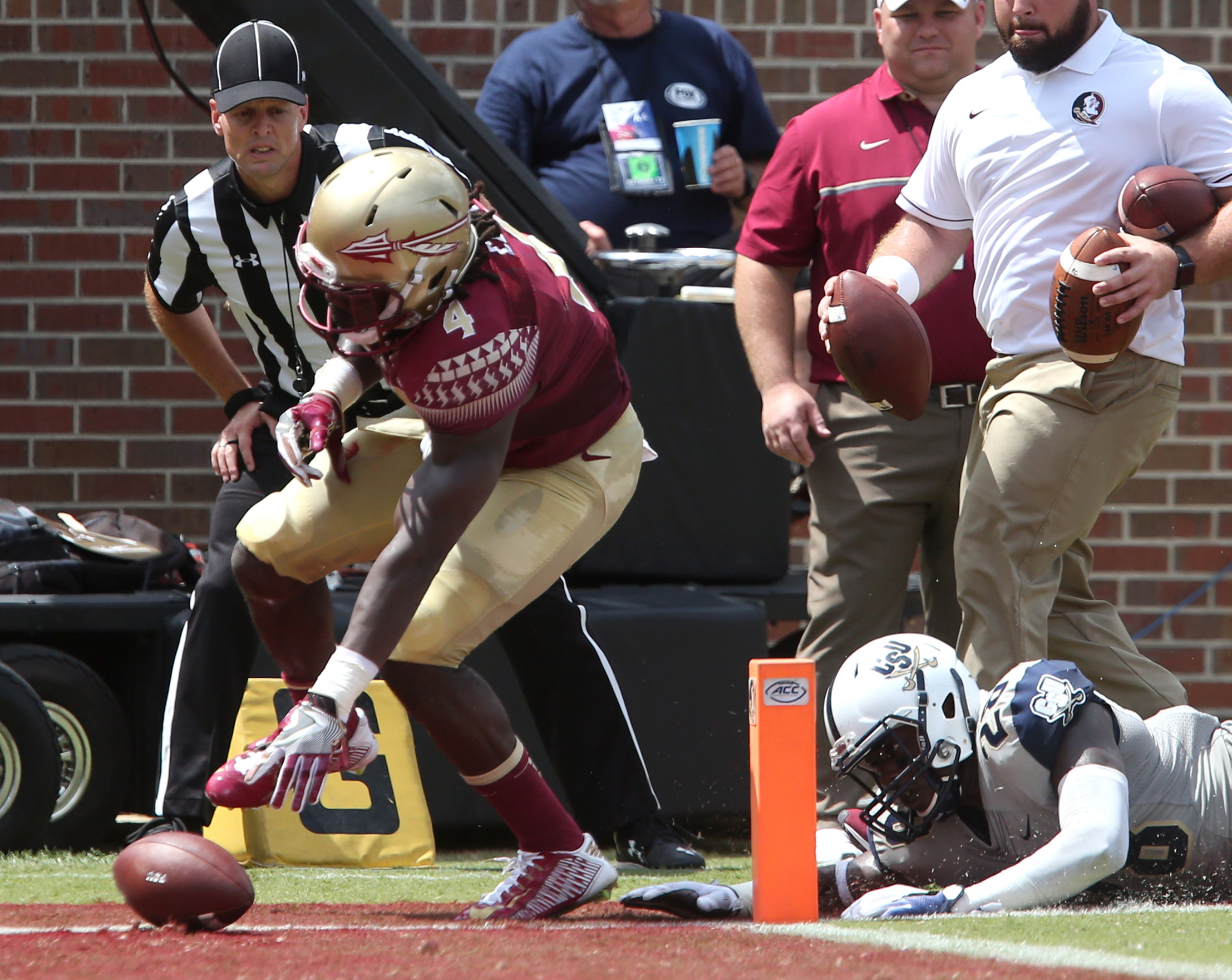 Florida State's Davin Cook tries to squeeze the ball past the pylon for a touchdown as Charleston Southern's Larenzo Mathis defends in the first half of an NCAA college football game, Saturday, Sept. 10, 2016, in Tallahassee, Fla. (AP Photo/Steve Cannon)
