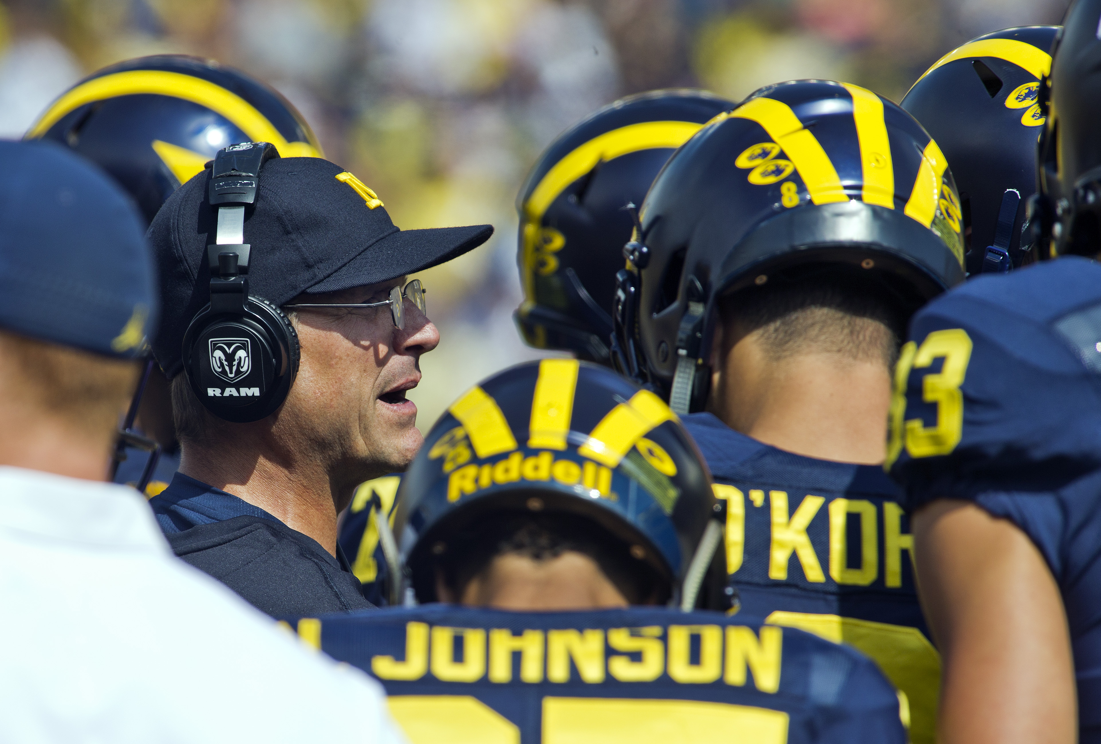 Michigan head coach Jim Harbaugh, left, huddles with his offense in the fourth quarter of an NCAA college football game against Central Florida at Michigan Stadium in Ann Arbor, Mich., Saturday, Sept. 10, 2016. Michigan won 51-14. (AP Photo/Tony Ding)