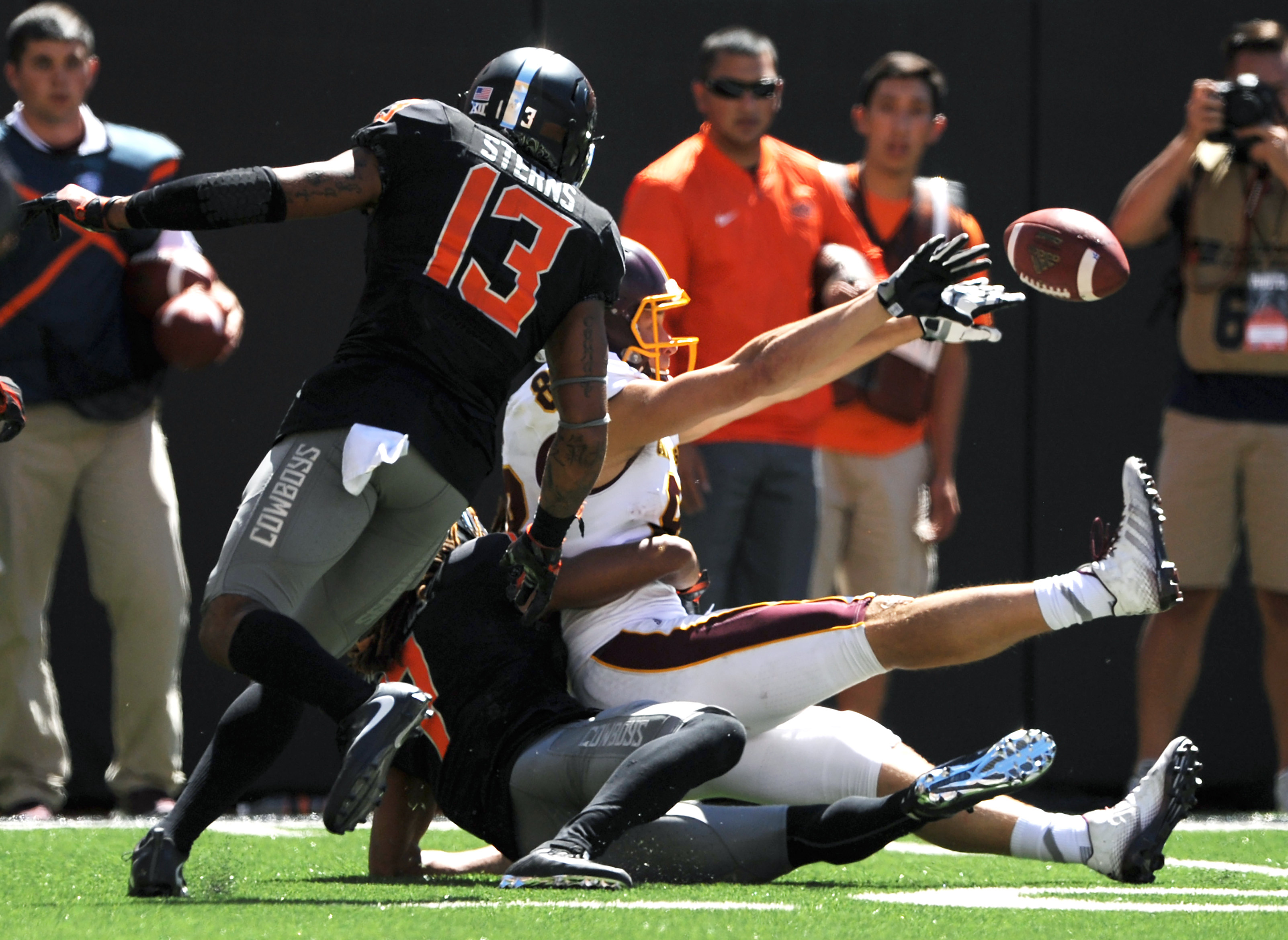 Oklahoma State safety Jordan Sterns, left, watches as Central Michigan wide receiver Jesse Kroll, right, being tackled by Oklahoma State corner back Ramon Richards, bottom, tosses the ball back to Central Michigan wide receiver Cory Willis resulting in a