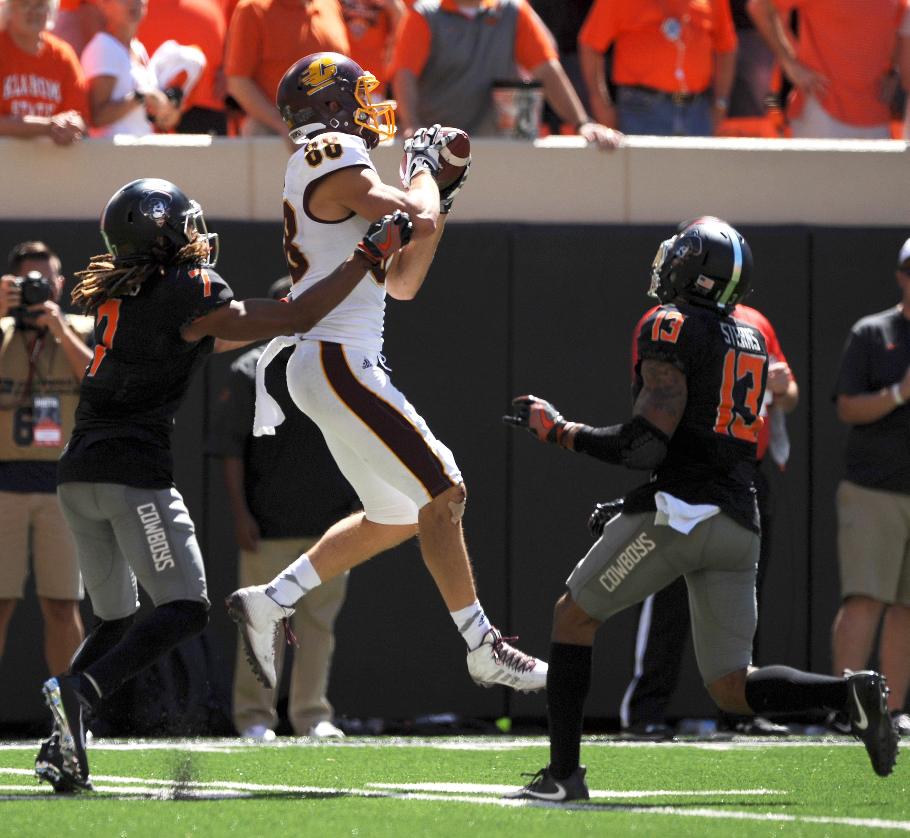 Oklahoma State safety Jordan Sterns, right, watches as Central Michigan wide receiver Jesse Kroll, center, catches a pass while being tackled by Oklahoma State corner back Ramon Richards, during the final play of an NCAA college football game in Stillwate