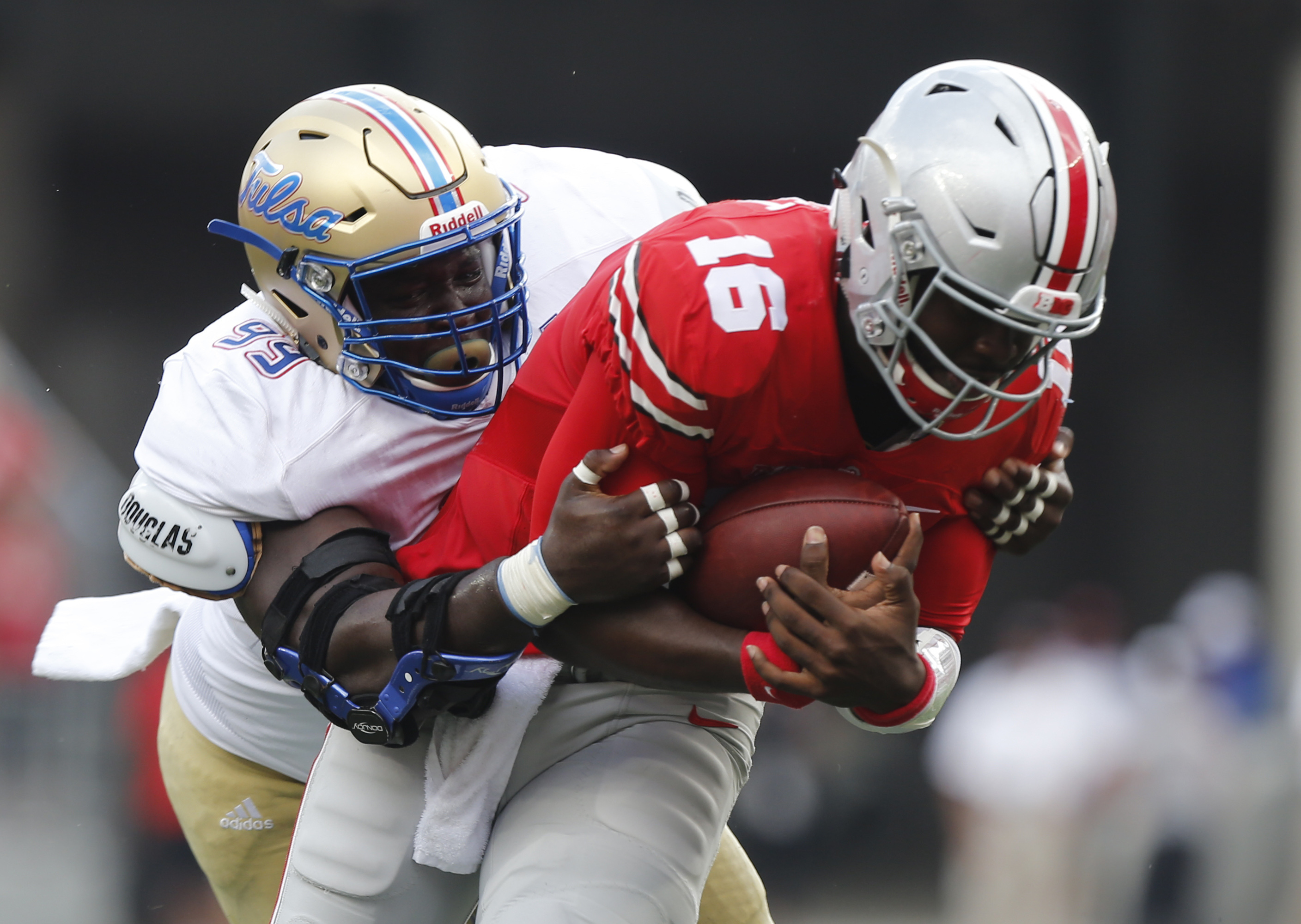Tulsa defensive lineman Jerry Uwaezuoke, left, tackles Ohio State quarterback J.T. Barrett during the first half of an NCAA college football game, Saturday, Sept. 10, 2016, in Columbus, Ohio. (AP Photo/Jay LaPrete)