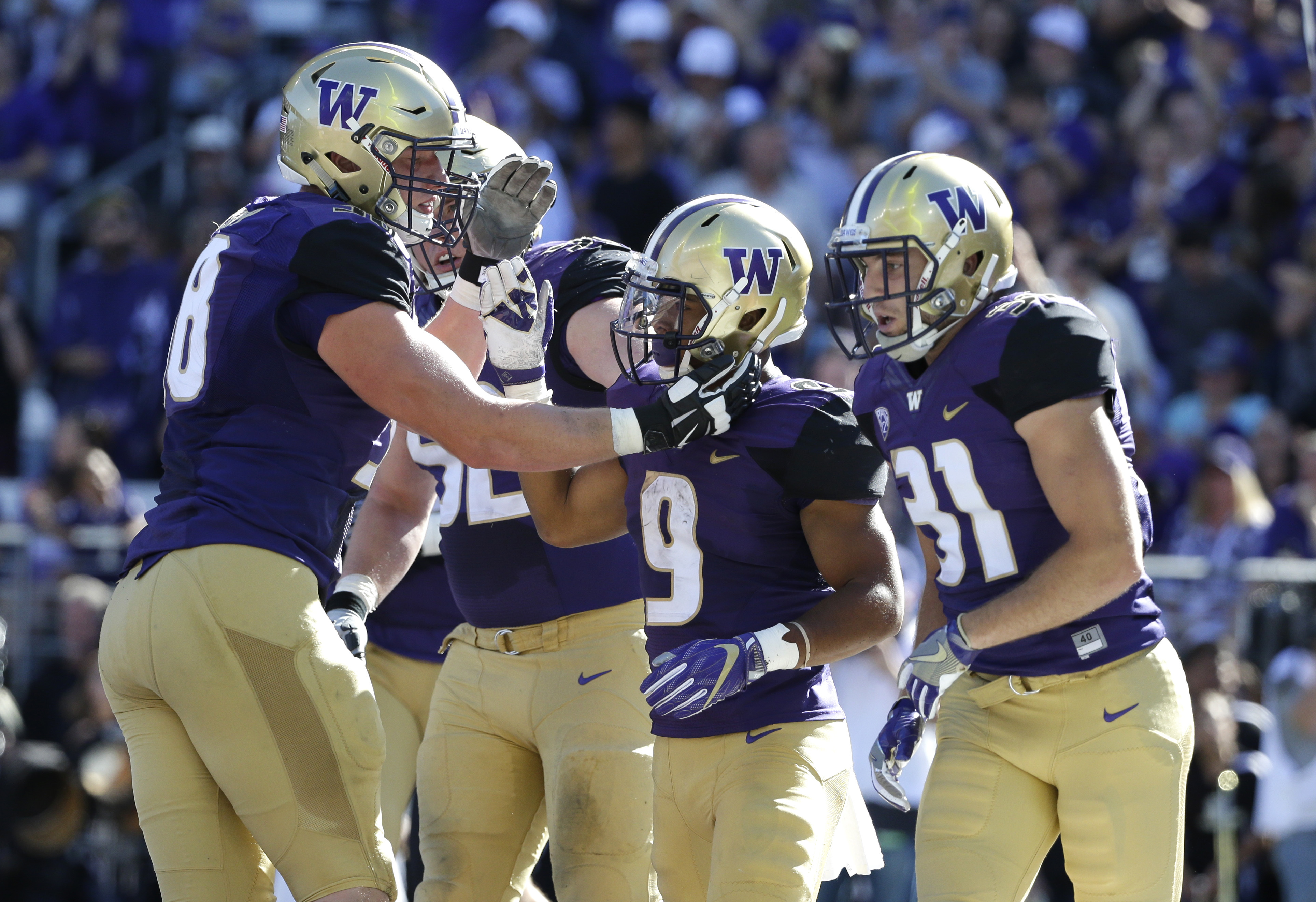 Teammates greet Washington running back Myles Gaskin (9) after Gaskin scored a touchdown against Idaho in the first half of an NCAA college football game, Saturday, Sept. 10, 2016, in Seattle. (AP Photo/Ted S. Warren)