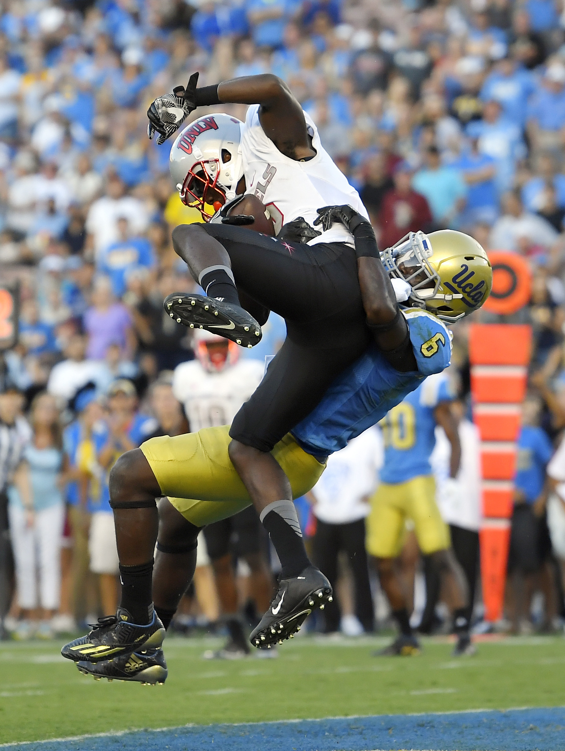 UNLV wide receiver Mekhi Stevenson, left, is pulled down by UCLA defensive back Adarius Pickett after making a touchdown catch during the first half of a college football game, Saturday, Sept. 10, 2016, in Pasadena, Calif. (AP Photo/Mark J. Terrill)