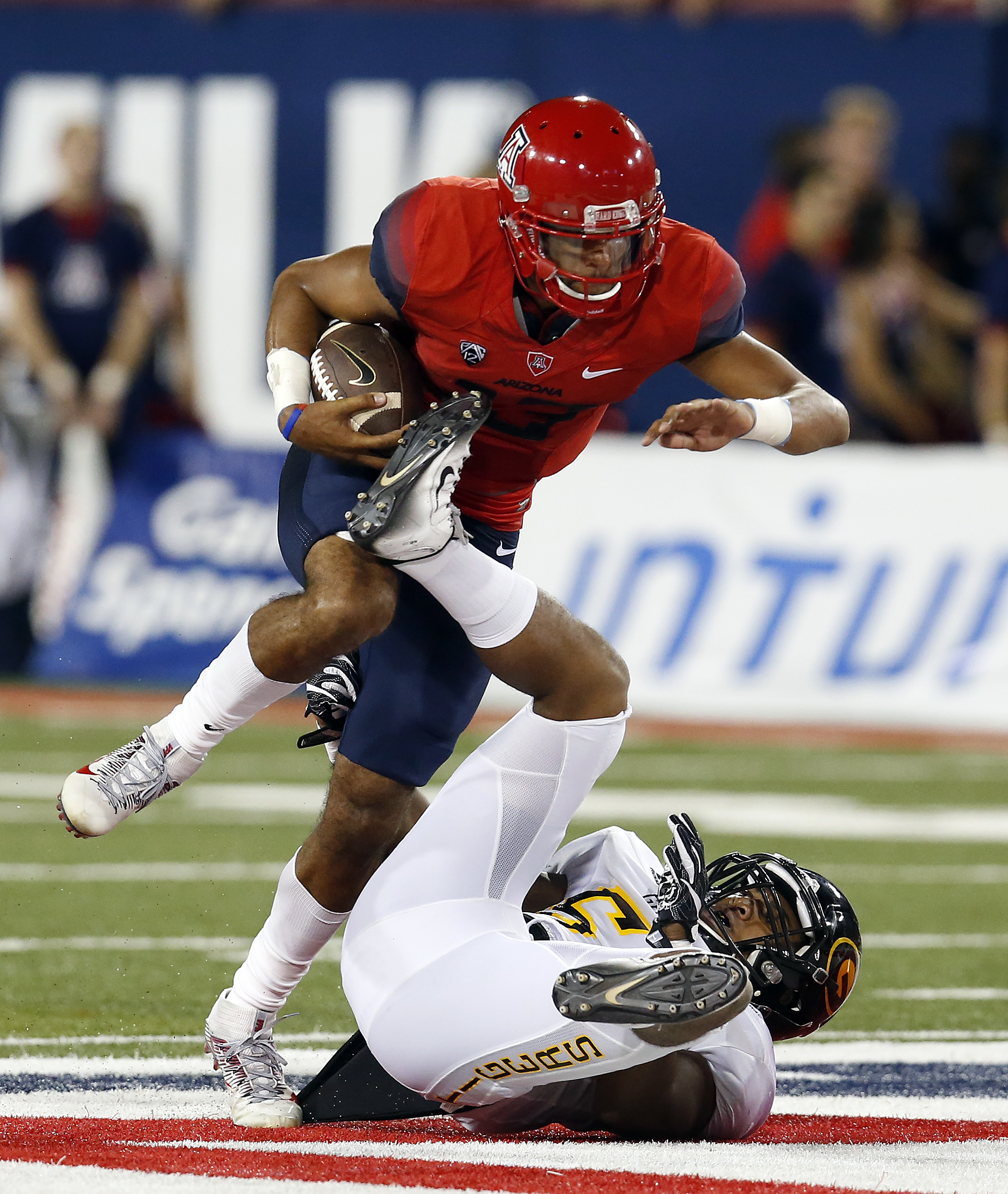 Arizona quarterback Brandon Dawkins (13) runs over Grambling State linebacker Christian Bailey (50) during the first half of an NCAA college football game, Saturday, Sept. 10, 2016, in Tucson, Ariz. (AP Photo/Rick Scuteri)