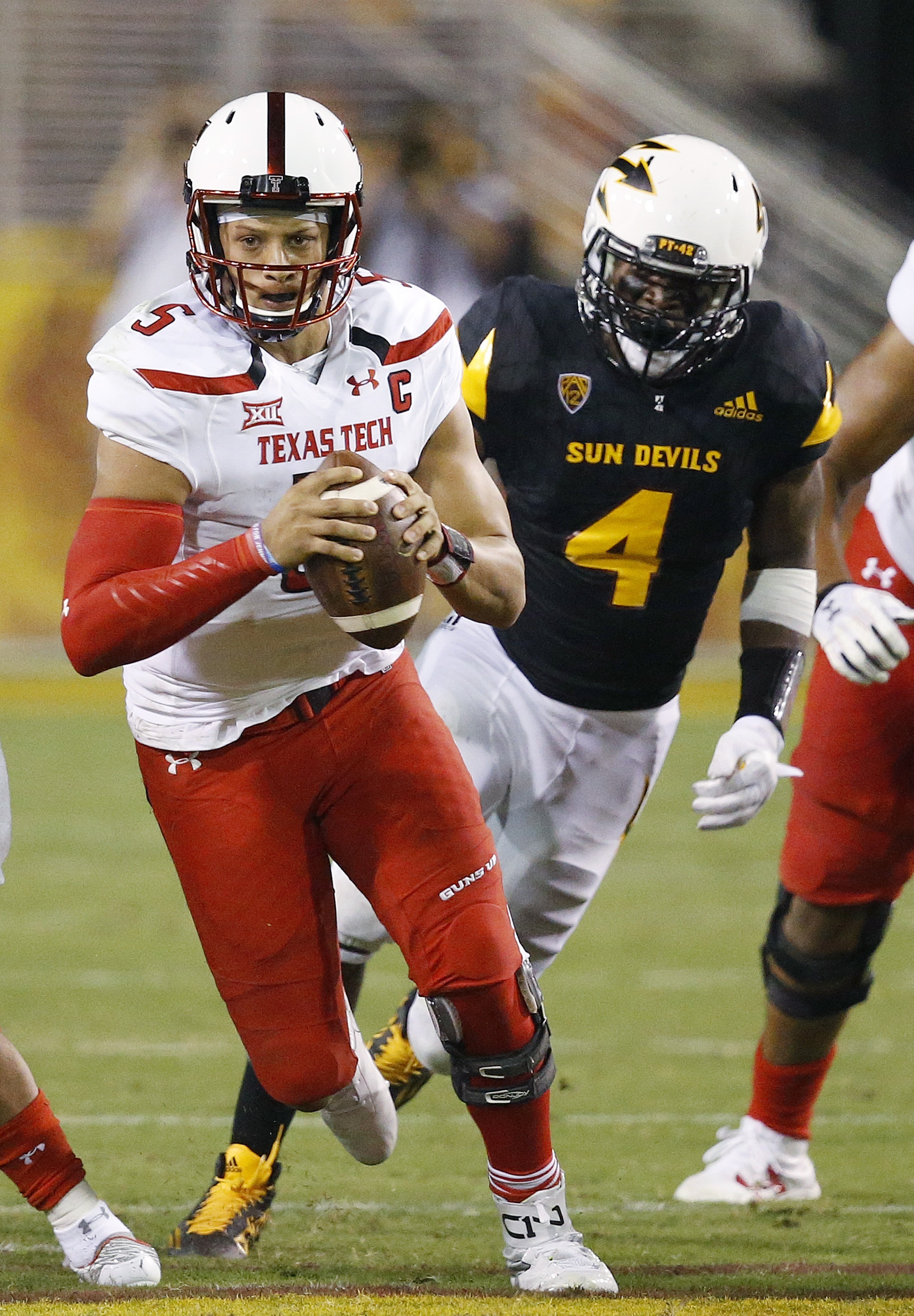 Texas Tech's Patrick Mahomes II, left, runs with the ball as he gets past Arizona State's Koron Crump (4) during the first half of an NCAA college football game Saturday, Sept. 10, 2016, in Tempe, Ariz. (AP Photo/Ross D. Franklin)