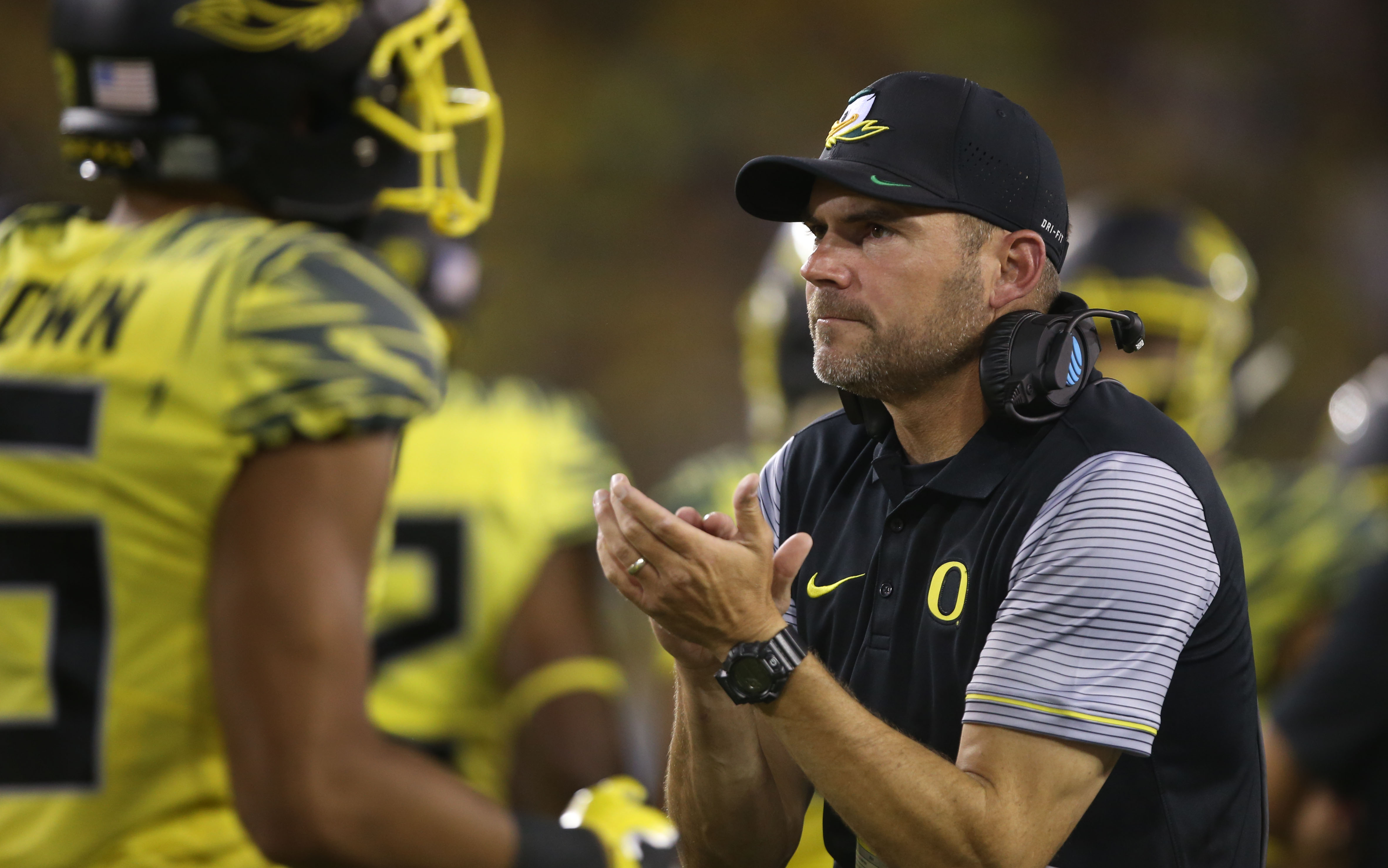 Oregon head coach Mark Helfrich, right, applauds his team as they return to the sidelines after scoring a touchdown against Virginia during the second quarter of an NCAA college football game Saturday, Sept. 10, 2016 in Eugene, Ore. (AP Photo/Chris Pietsc