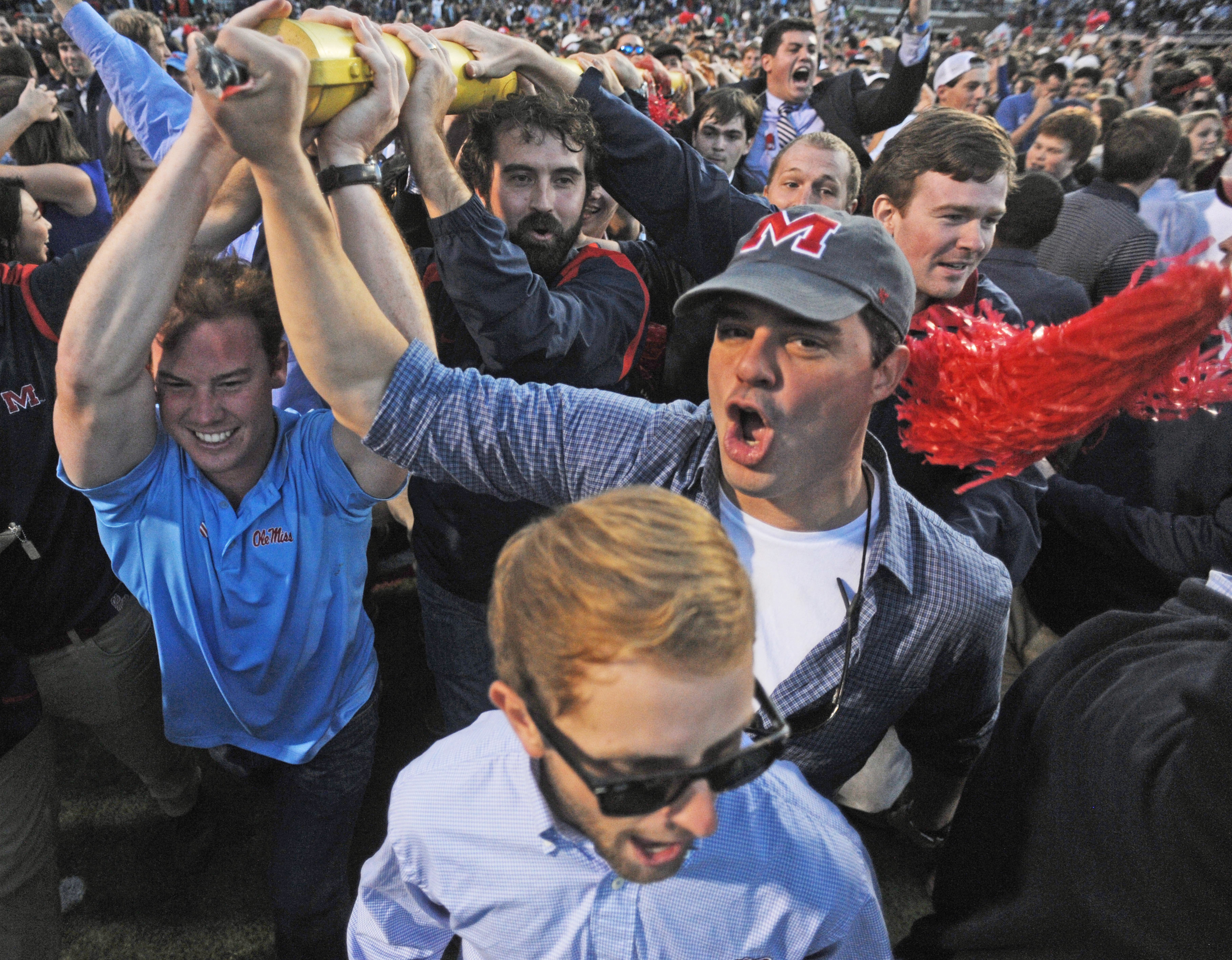 FILE - In this Oct. 4, 2014, file photo, Mississippi fans carry a goal post out of the stadium following the team's 23-17 win over Alabama in an NCAA college football game in Oxford, Miss. The Rebels are the only team to top the Crimson Tide in each of th