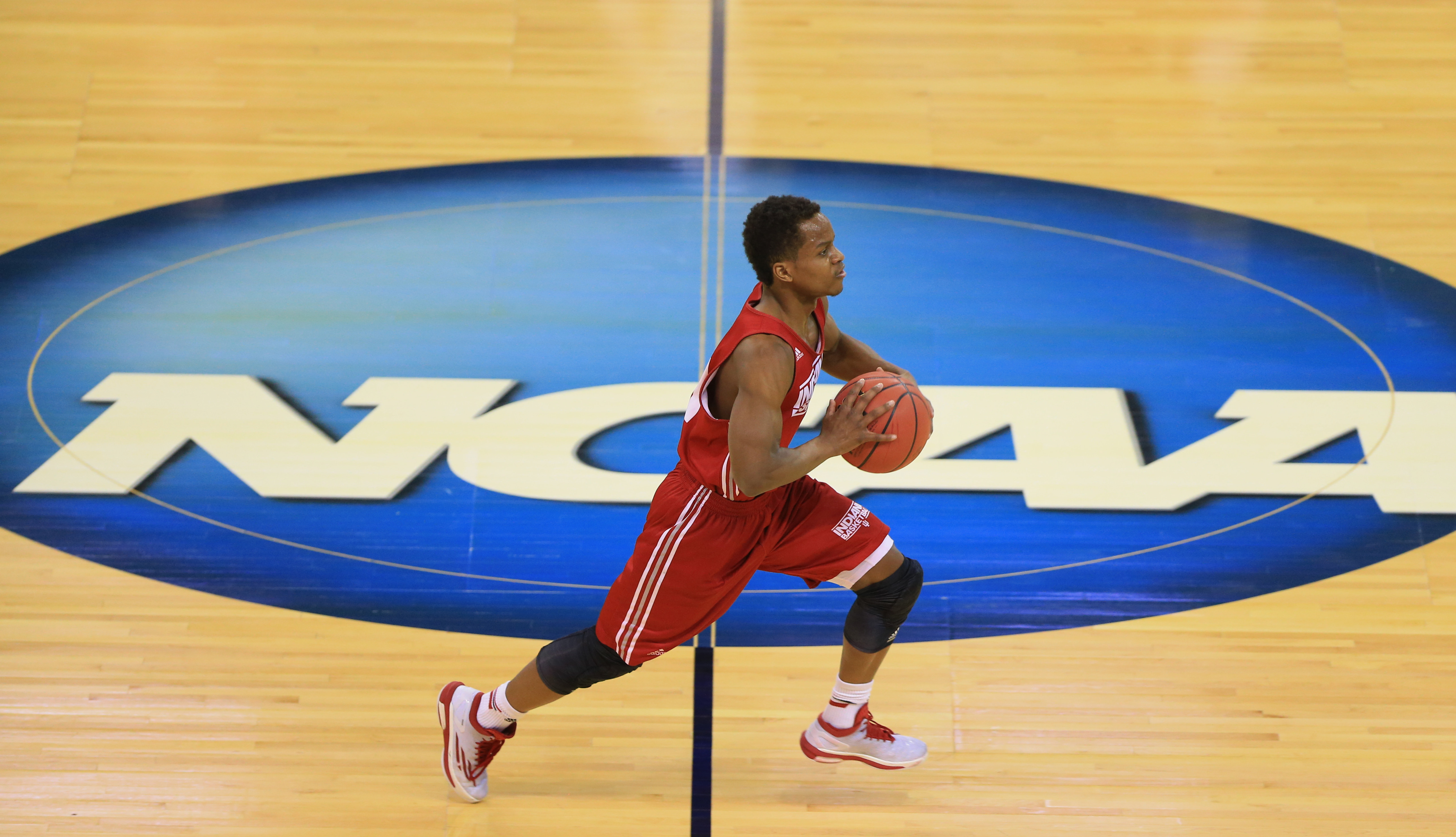 Indiana's Kevin Yogi Ferrell (11) runs past the NCAA logo during practice for an NCAA college basketball tournament second round game in Omaha, Neb., Thursday, March 19, 2015. Indiana plays Wichita State on Friday. (AP Photo/Nati Harnik)