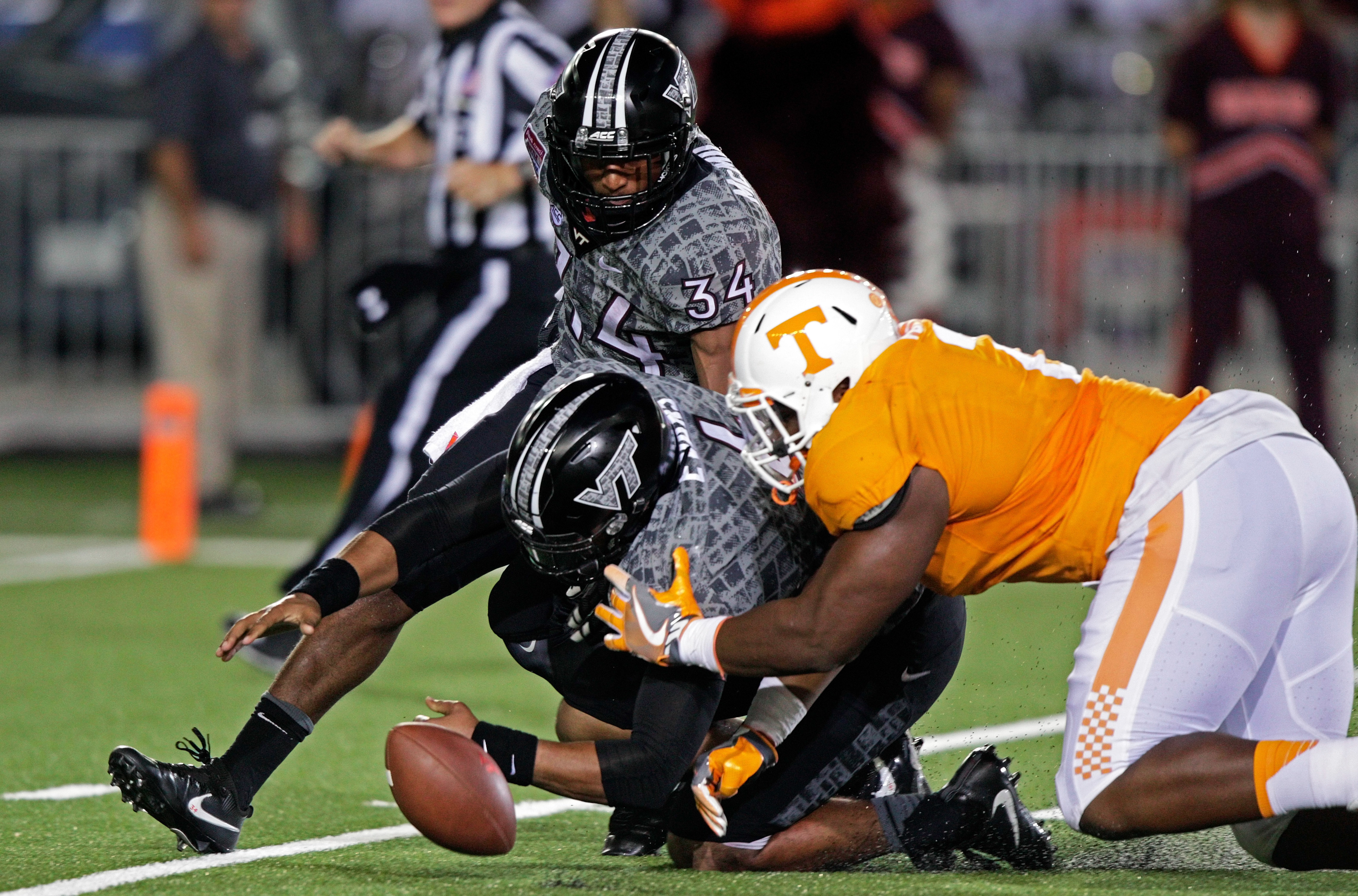 FILE- In this Saturday, Sept. 10, 2016, file photo,  Tennessee defensive lineman Shy Tuttle (2) and Virginia Tech wide receiver Isaiah Ford (1) and running back Travon McMillian (34) vie for a fumble during the second half of an NCAA college football game