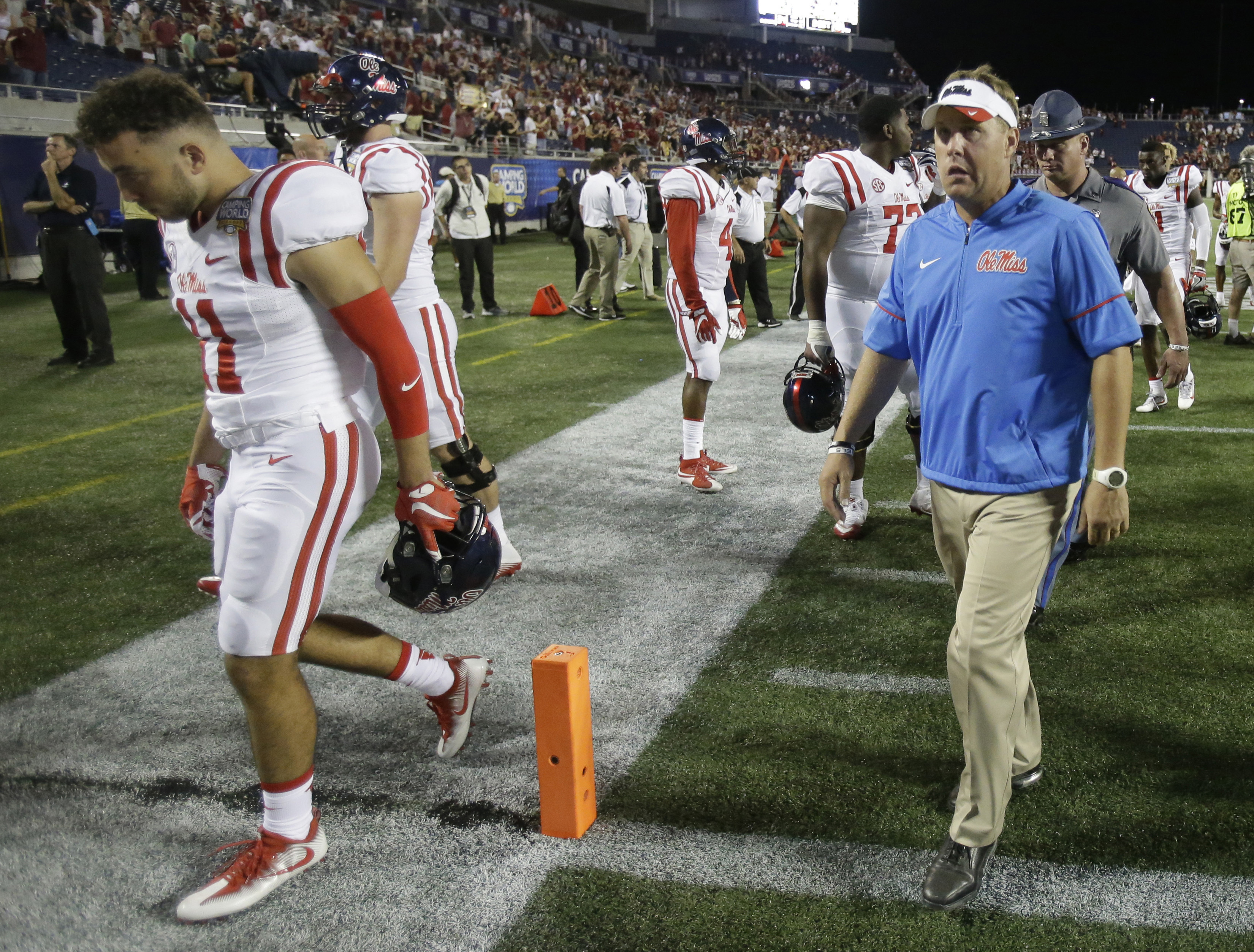 FILE - In this Sept. 6, 2016, file photo, Mississippi head coach Hugh Freeze, right, leaves the field with players after losing to Florida State 45-34 in an NCAA college football game, in Orlando, Fla. Oklahoma and Mississippi entered this season with leg