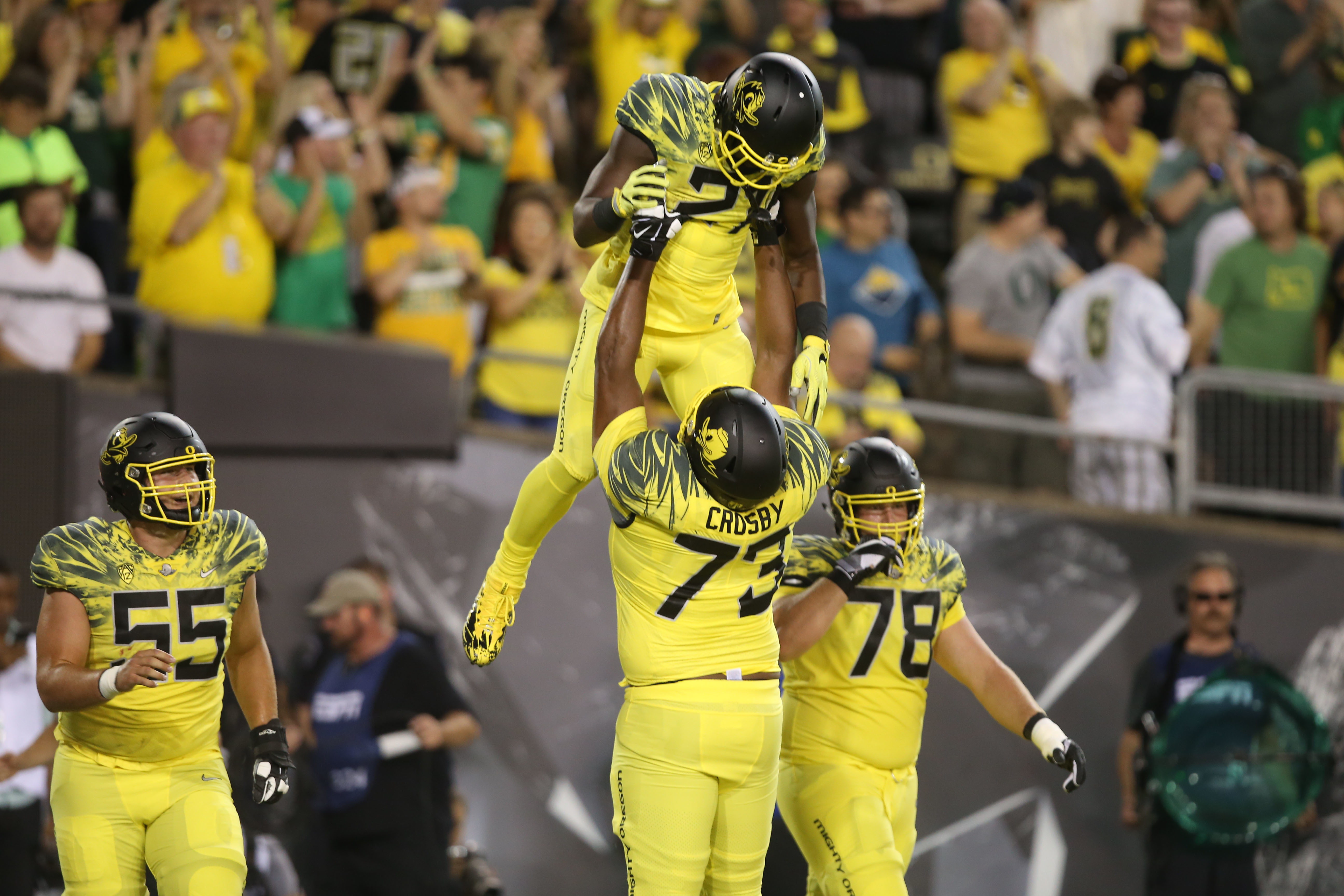 FILE - In this Sept. 10, 2016, file photo, Oregon's Royce Freeman, center, is hoisted in the air by teammate Tyrell Crosby after scoring a touchdown against Virginia during the first quarter of an NCAA college football game in Eugene, Ore. Freeman got his
