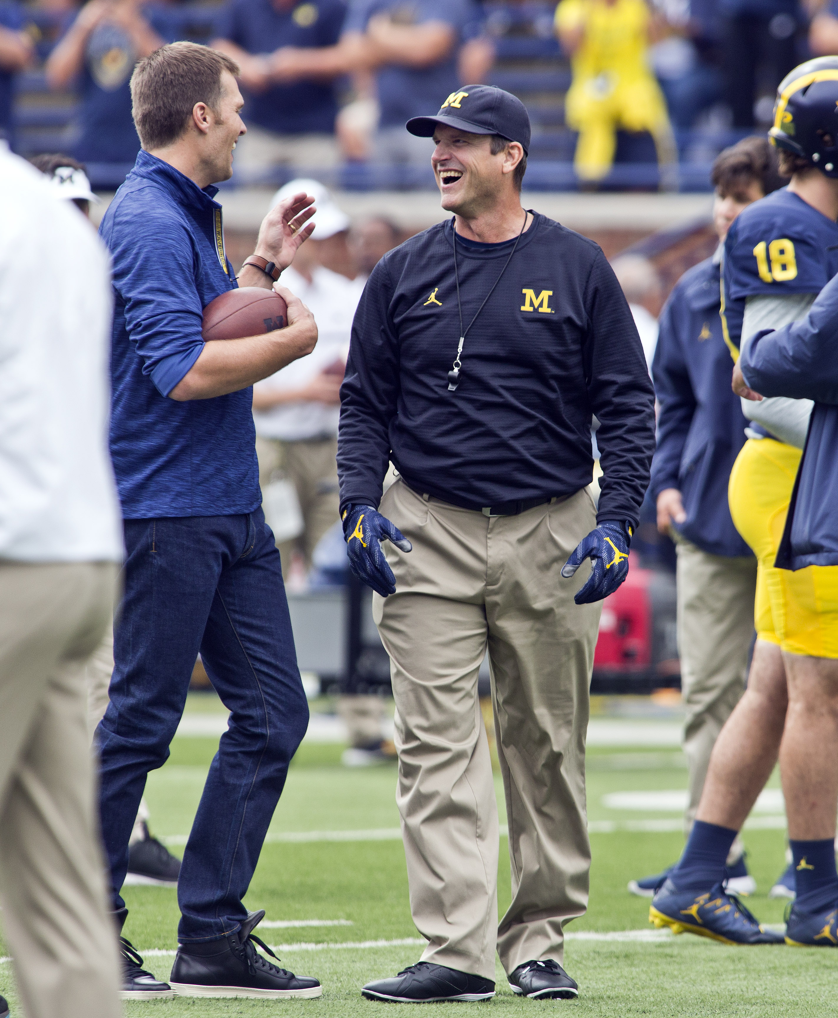 Former Michigan and currently suspended New England Patriots quarterback Tom Brady, left, shares a laugh with Michigan head coach Jim Harbaugh, right,  before an NCAA college football game against Colorado at Michigan Stadium in Ann Arbor, Mich., Saturday