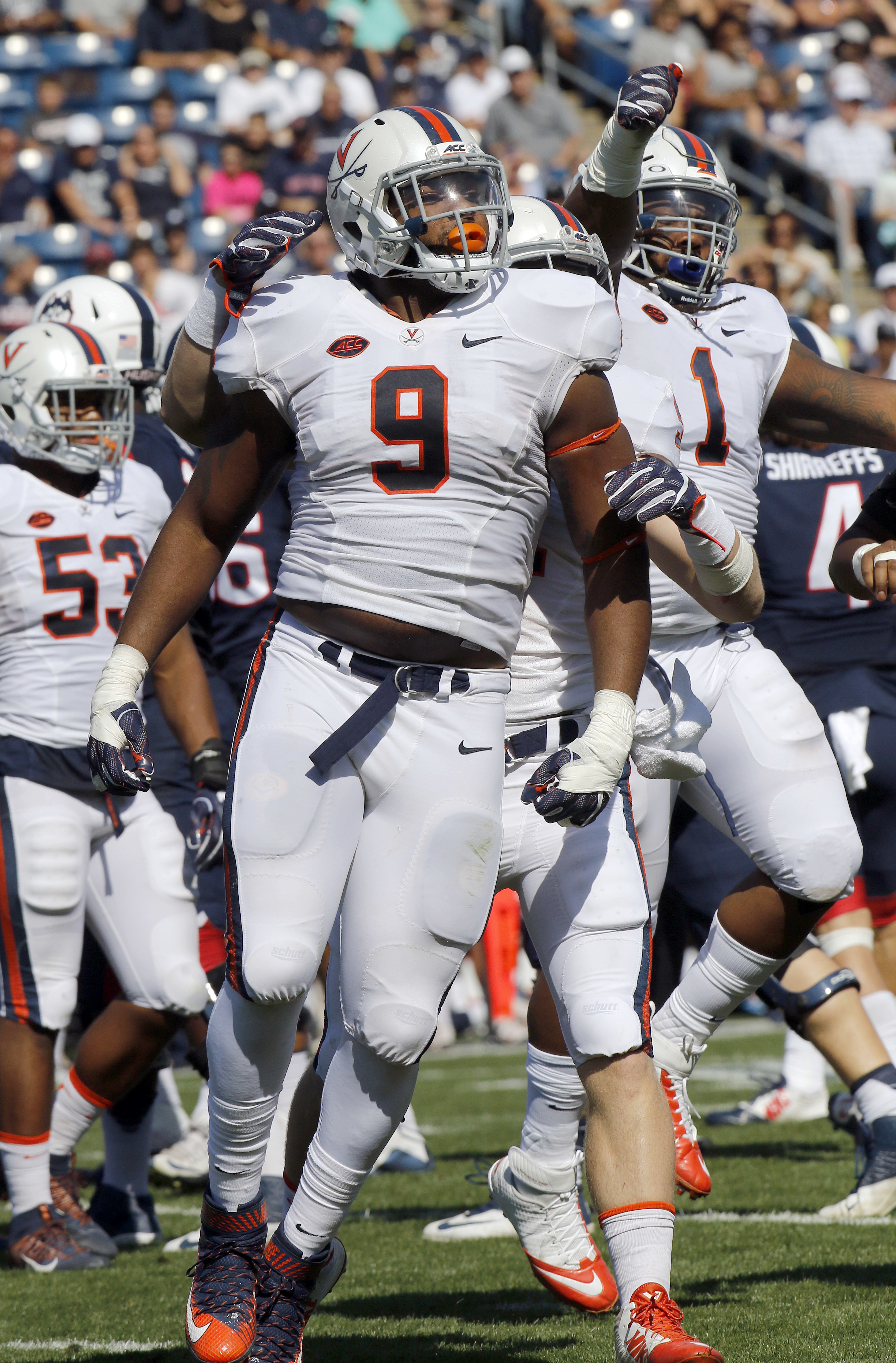 Virginia's Andrew Brown (9) and Donte Wilkins (1) celebrate a sack of Connecticut quarterback Bryant Shirreffs in the first half of an NCAA college football game Saturday, Sept. 17, 2016, in East Hartford, Conn. (AP Photo/Bill Sikes)