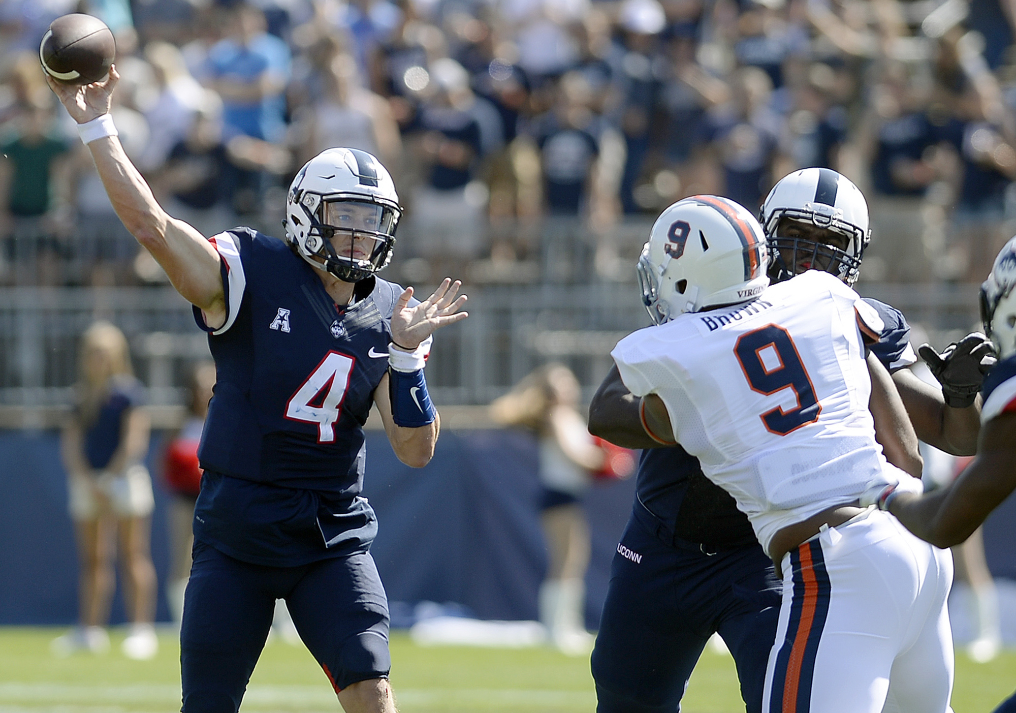 Connecticut quarterback Bryant Shirreffs (4) passes against the rush by Virginia's Andrew Brown (9) in the first half of an NCAA college football game Saturday, Sept. 17, 2016, in East Hartford, Conn. (AP Photo/Jessica Hill)