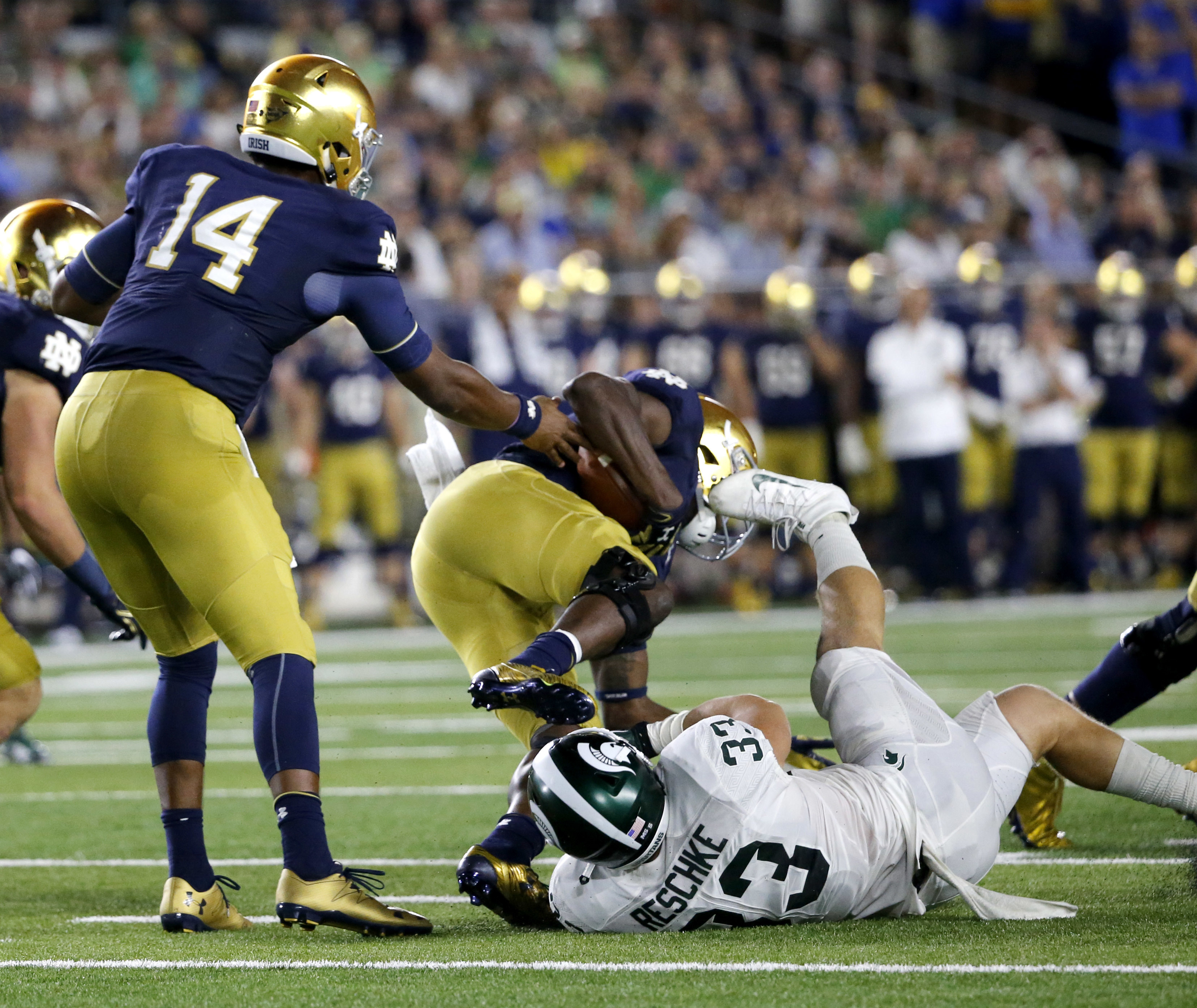 Michigan State linebacker Jon Reschke (33) trips Notre Dame running back Josh Adams after Adams got the handoff from quarterback DeShone Kizer during the second half of an NCAA college football game Saturday, Sept. 17, 2016, in South Bend, Ind. (AP Photo/
