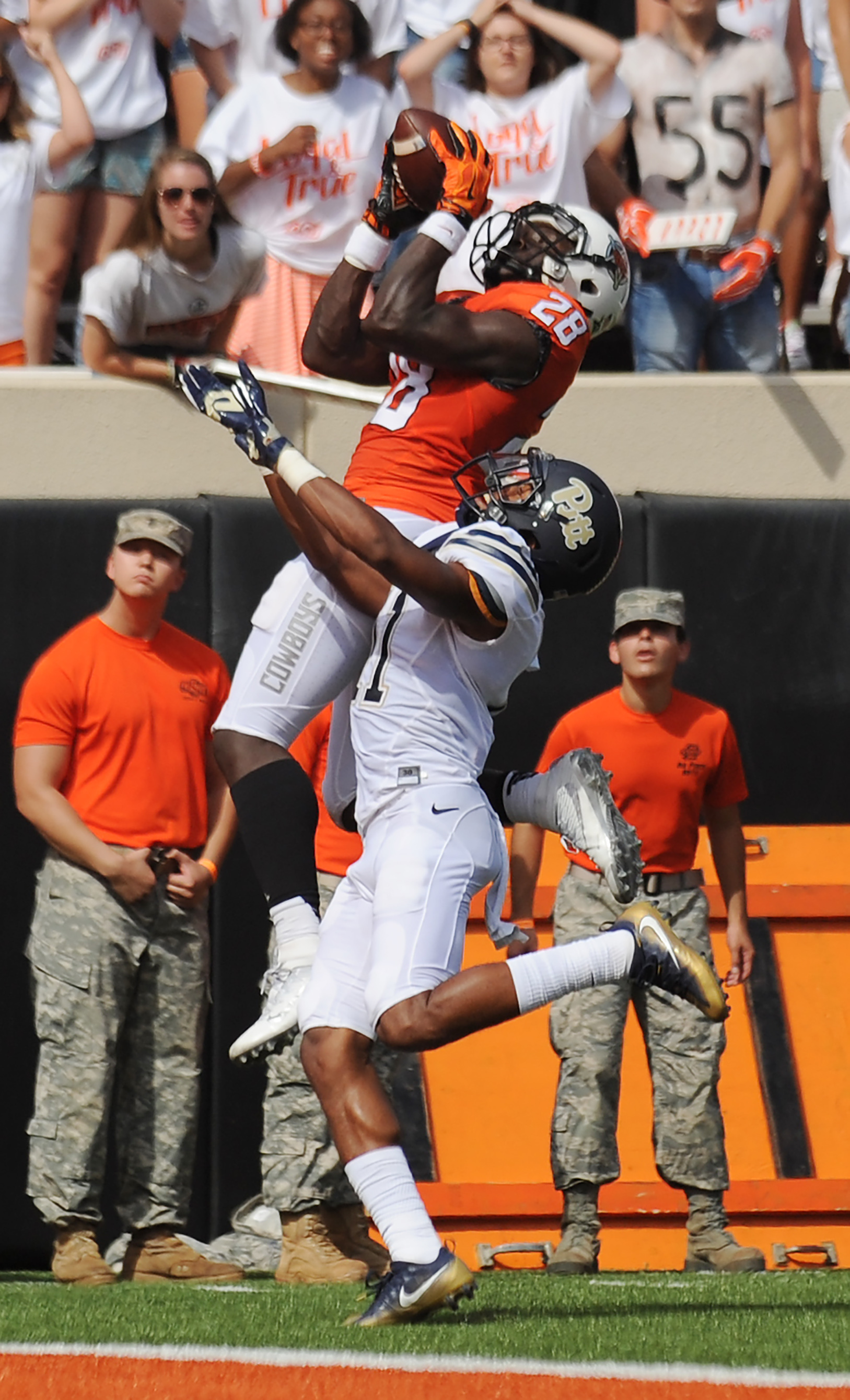 Oklahoma State wide receiver James Washington, top, catches a touchdown pass despite pressure from Pittsburgh defensive back Dane Jackson during the first half of an NCAA college football game in Stillwater, Okla., Saturday, Sept. 17, 2016. (AP Photo/Brod