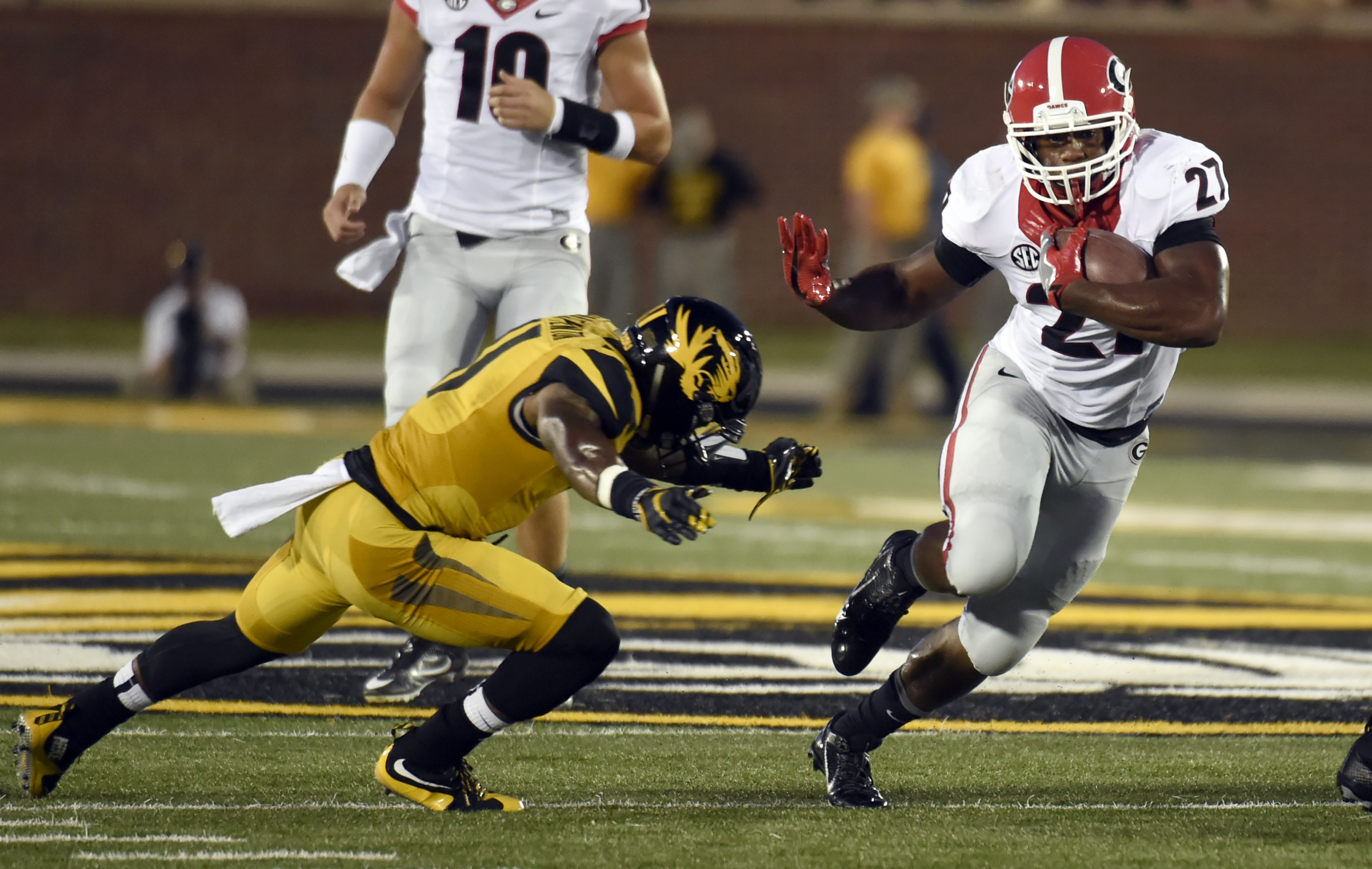 File-This Sept. 17, 2016, file photo shows Georgia running back Nick Chubb, right, running past Missouri defensive back Aarion Penton during the first half of an NCAA college football game in Columbia, Mo. Chubb is averaging 121 yards rushing per game and