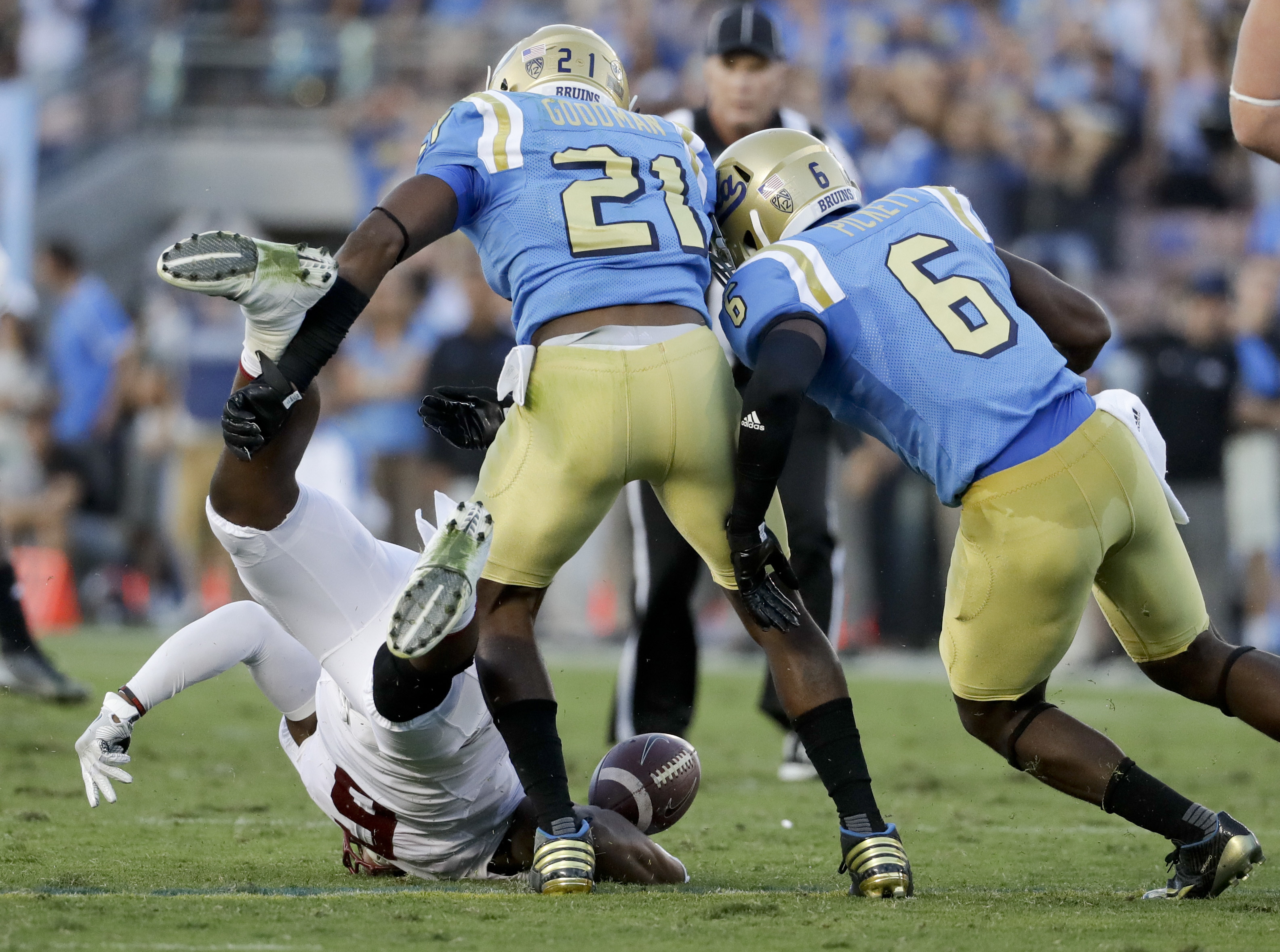 UCLA defensive back Adarius Pickett, right, and defensive back Tahaan Goodman, force a fumble by Stanford wide receiver Francis Owusu during the first half of an NCAA college football game in Pasadena, Calif., Saturday, Sept. 24, 2016. Owusu was injured o